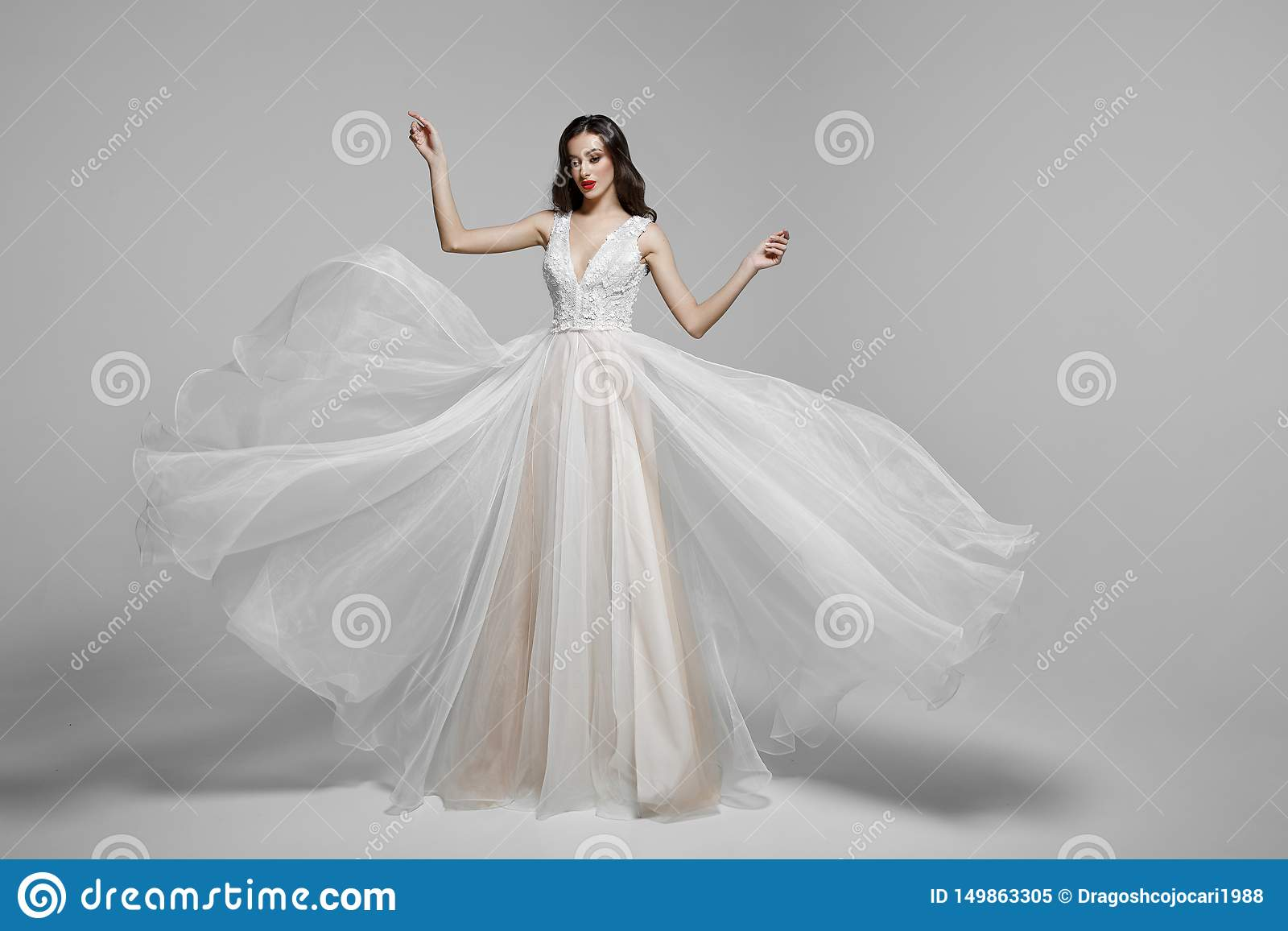 Beauty portrait of a young woman in wedding fashion long dress in waving flying fabric, cloth fluttering in wind.