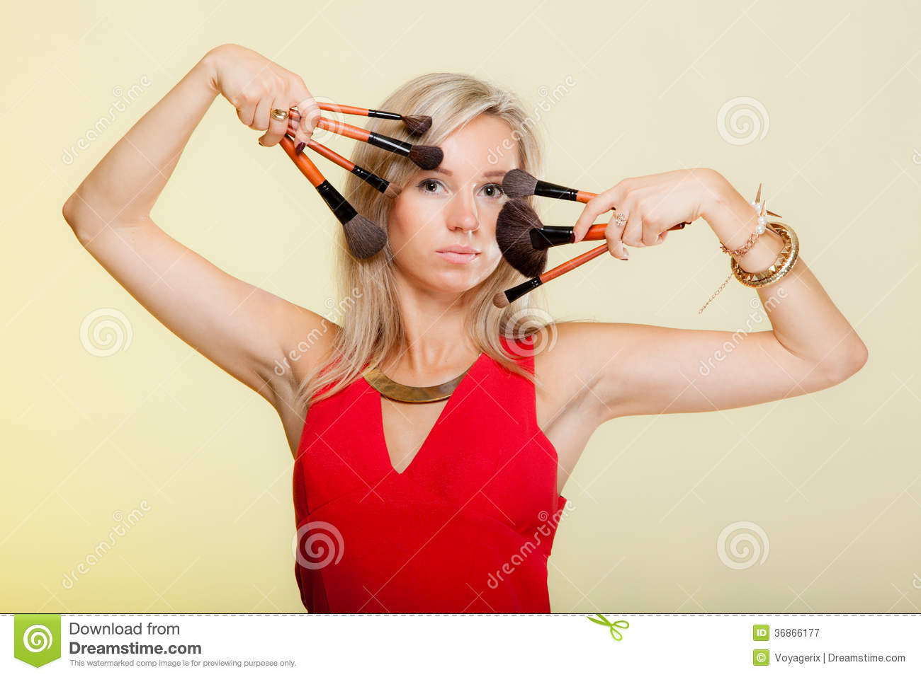 Beauty procedures, woman holds make-up brushes near face.