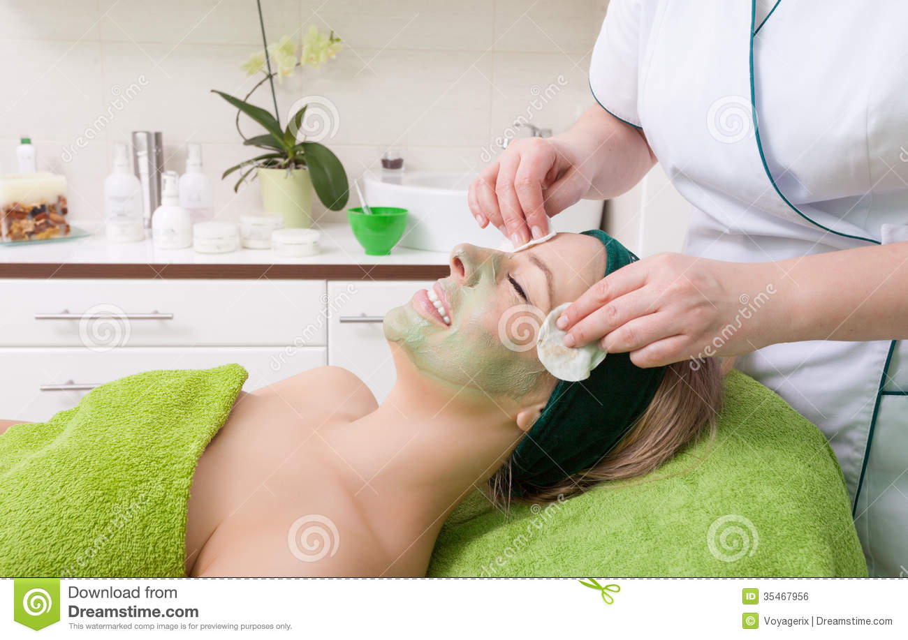 Beauty salon cosmetician removing facial mask from woman for A trial beauty treatment salon