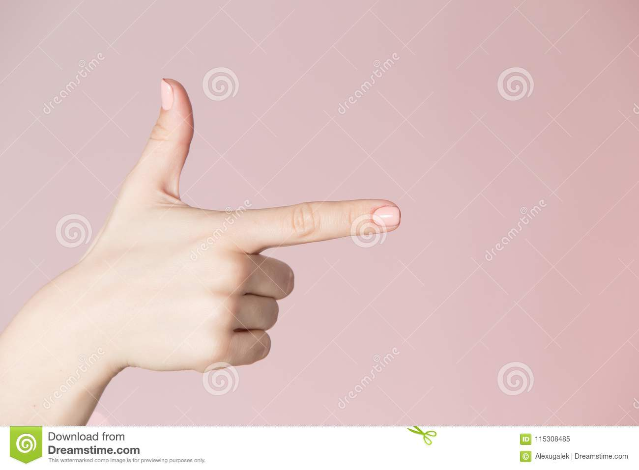 Beauty salon location theme. Woman hand with pink manicure showing gun sign