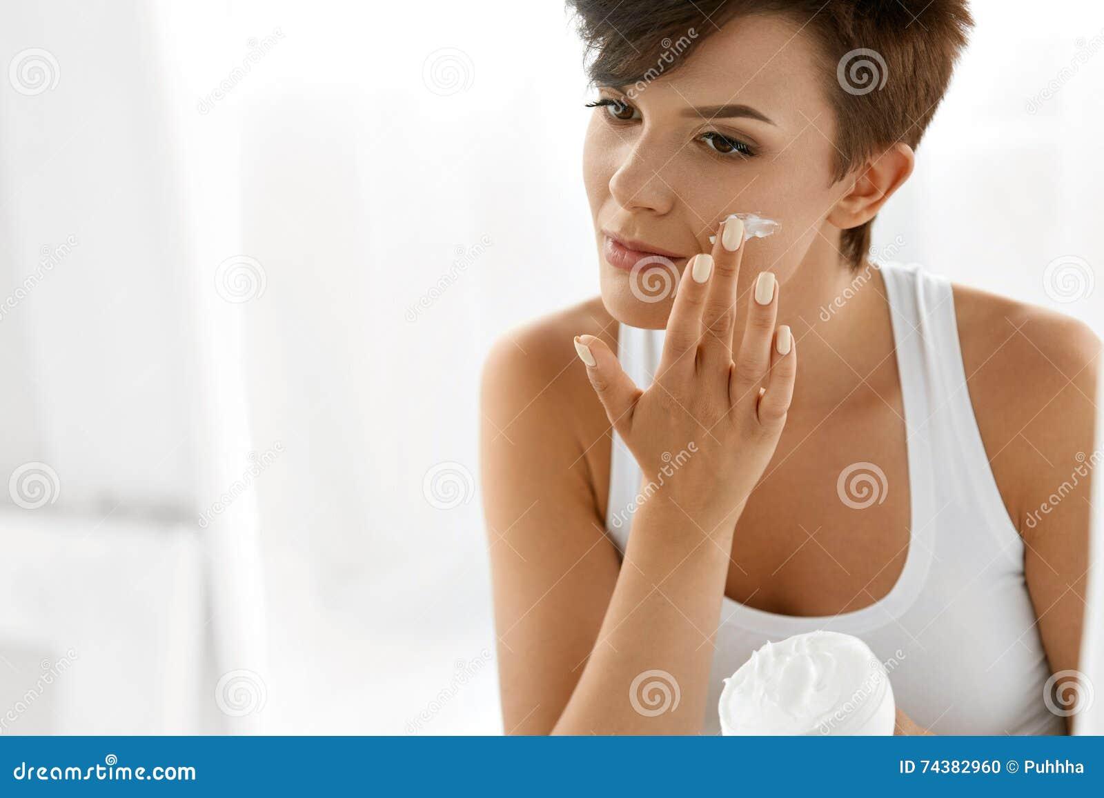 Beauty Skin Care. Beautiful Woman Applying Cosmetic Face Cream