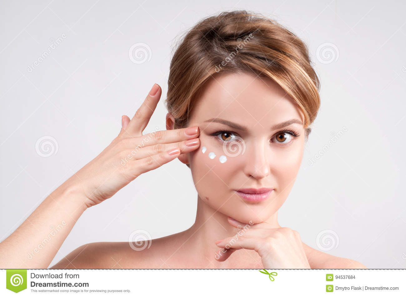 Beauty and skincare concept. Young woman applying moisturizer on face.