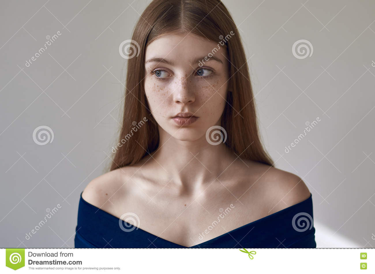 Beauty theme: portrait of a beautiful young girl with freckles on her face and wearing a blue dress on a white background in