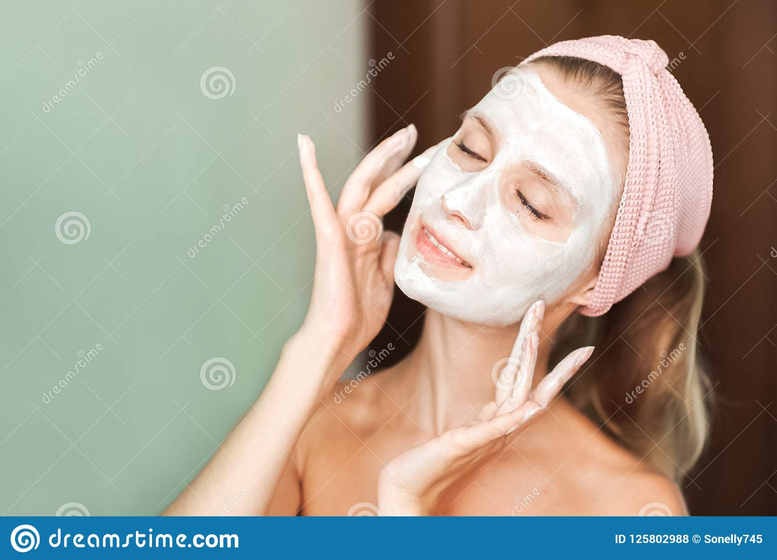 Beauty Treatments. Young woman is applying a mask, cream on her face close-up. Facial skin care portrait of a beautiful girl with