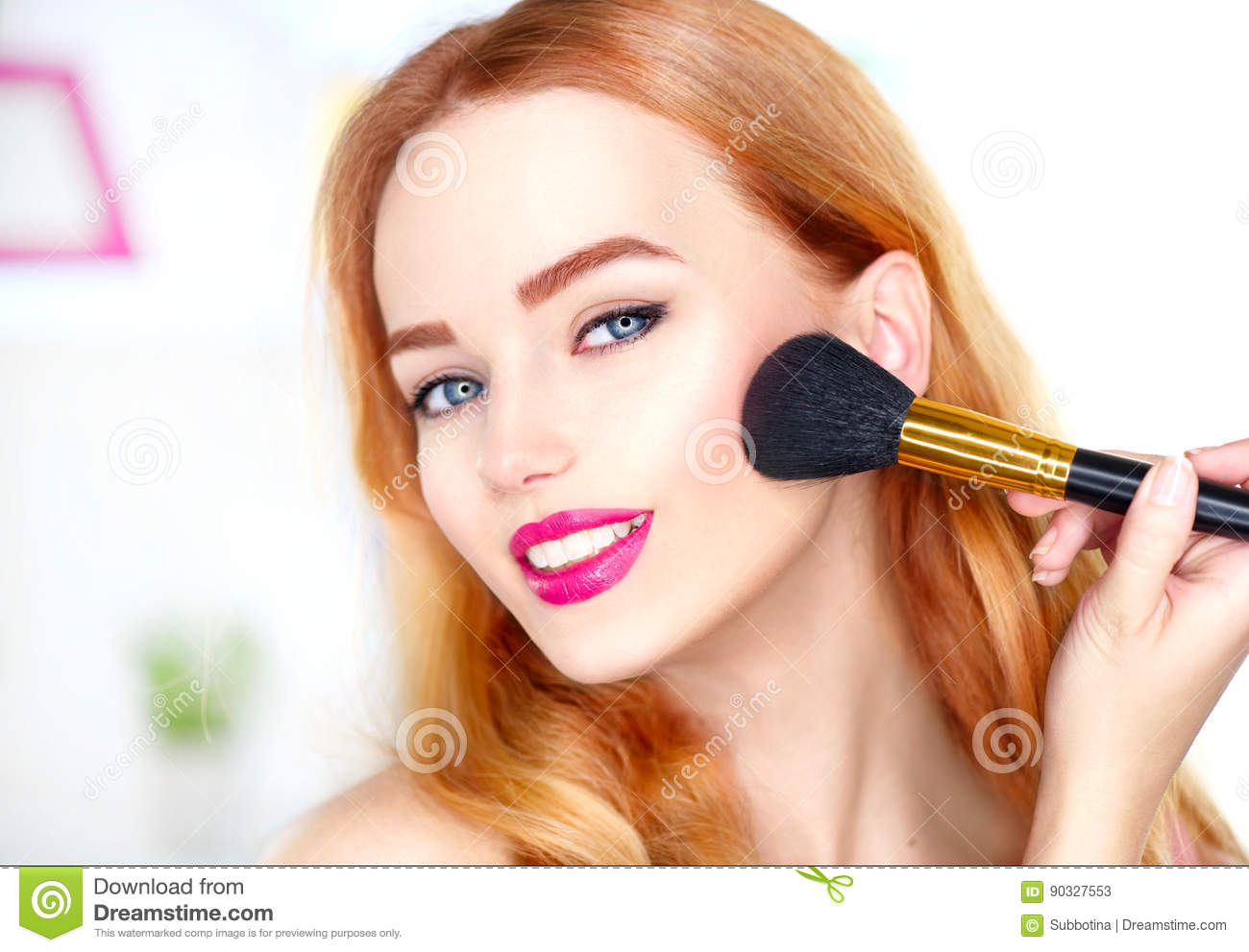 Beauty woman applying makeup. Beautiful girl looking in the mirror and applying cosmetic