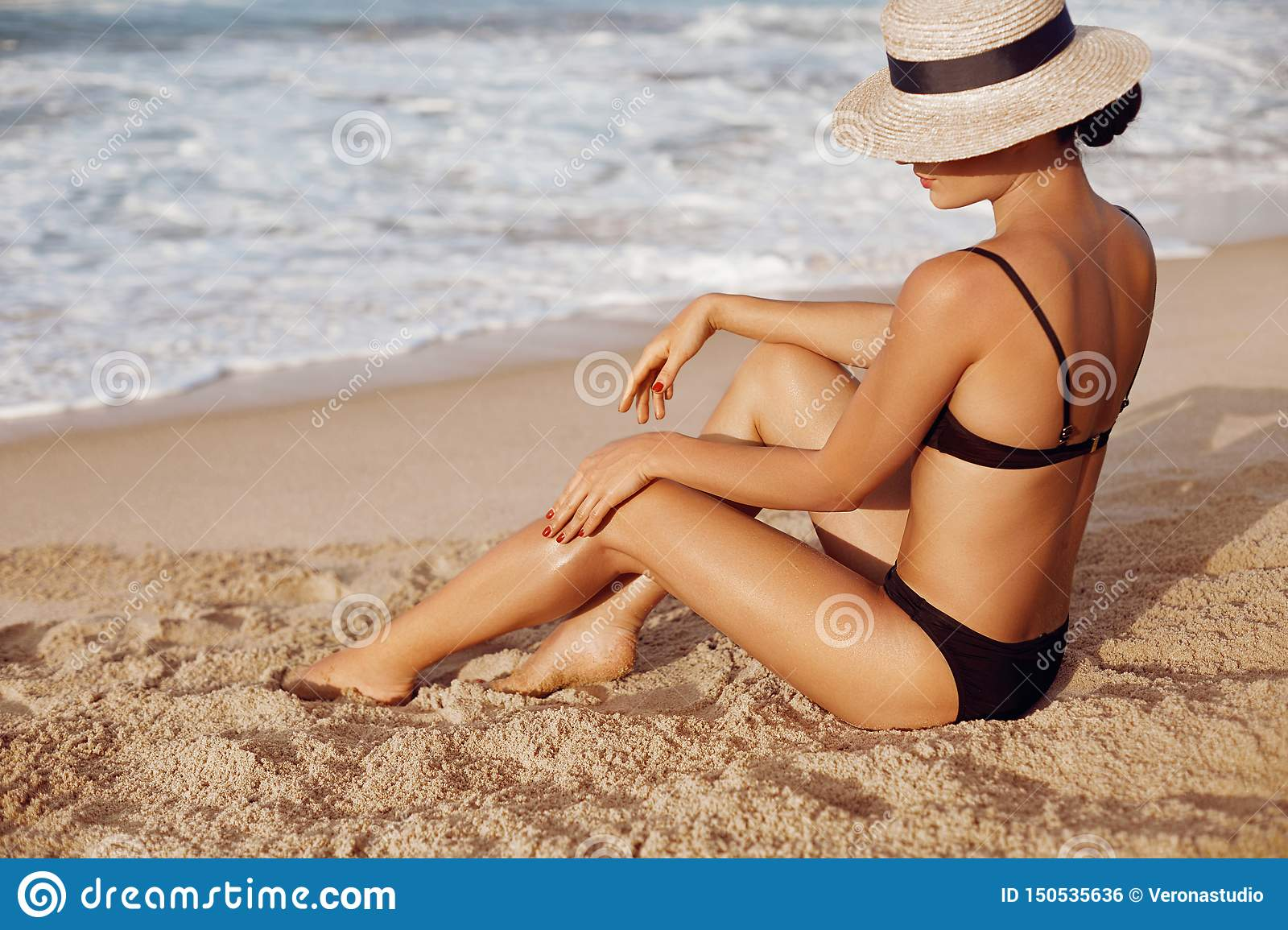 Beauty Woman applying sun cream lotion on legs. Skin cream. A Female smear sunscreen on beautiful legs on beach.