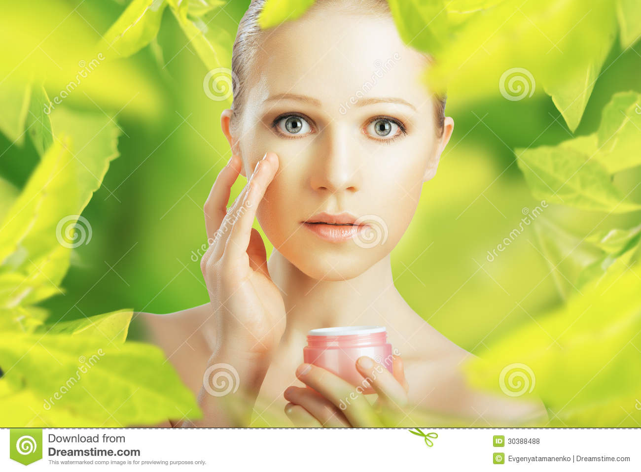 Beauty young woman with cream and a natural skin care in herbal green