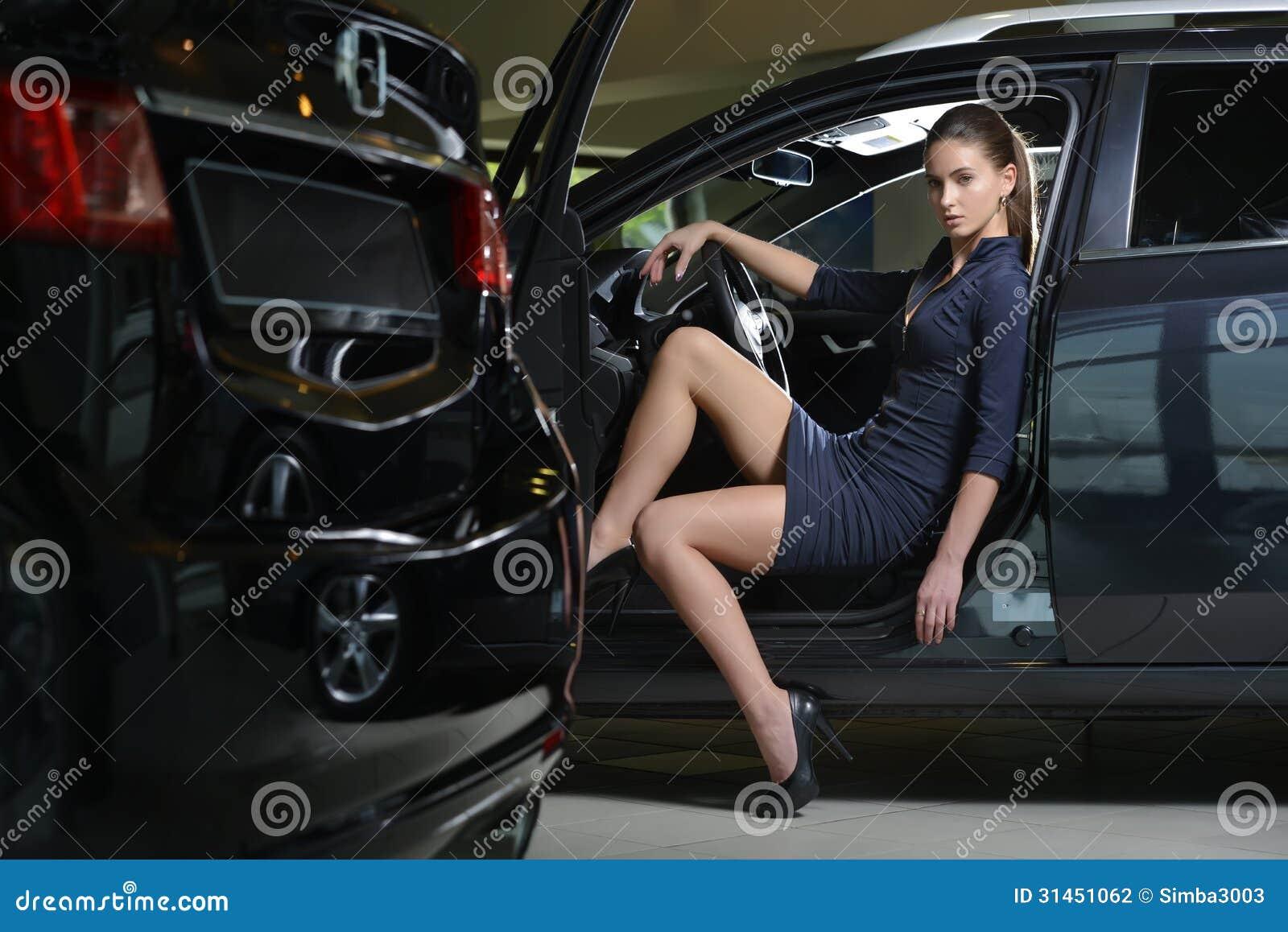 Beauty woman driver sitting inside her car with door open for Interieur de voiture de luxe