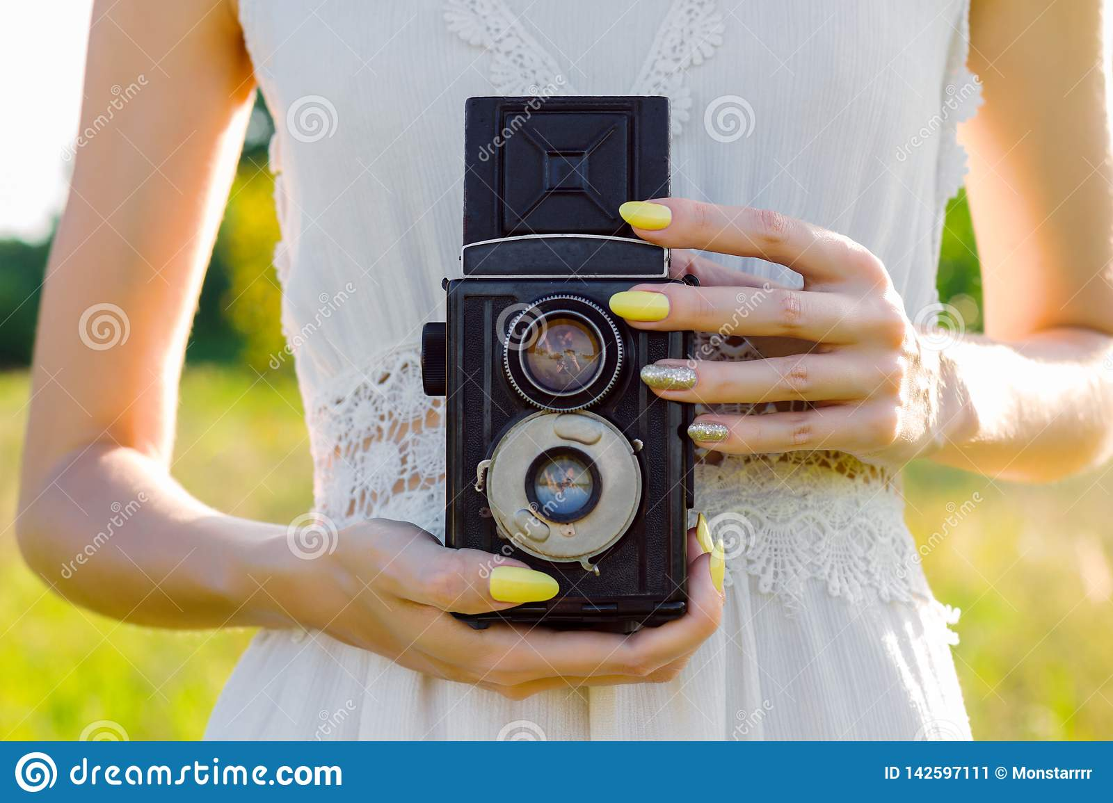 Beauty woman taking photo on retro camera outdoor in park in warm spring day