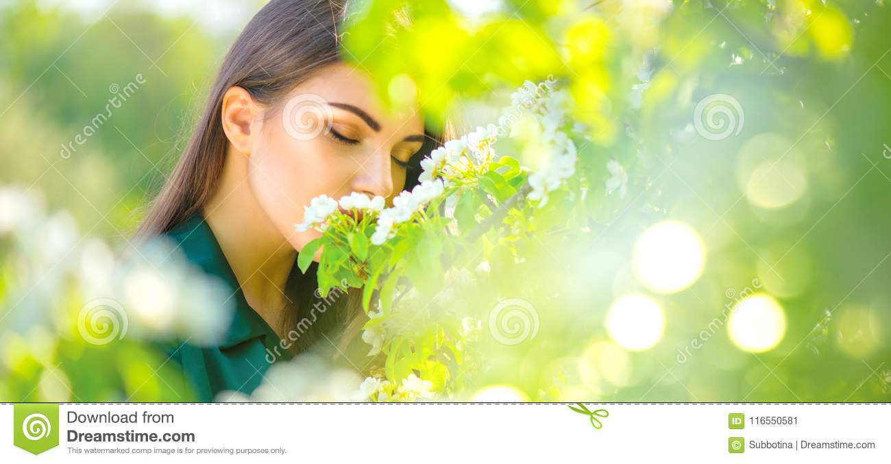 Beauty young woman enjoying nature in spring apple orchard, Happy beautiful girl in a garden with blooming fruit trees