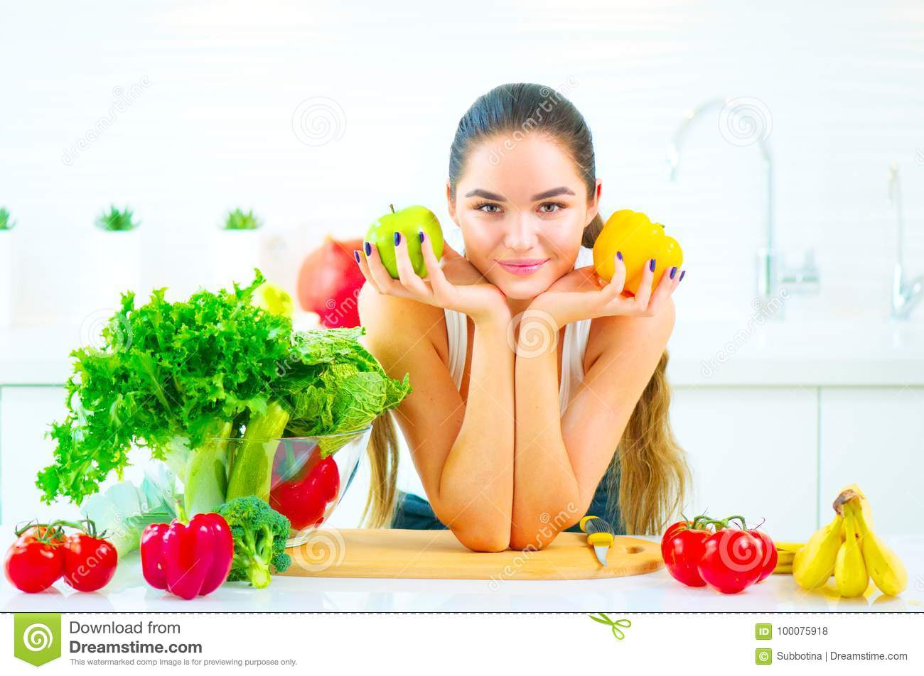 Beauty young woman holding fresh vegetables and fruits in her kitchen at home