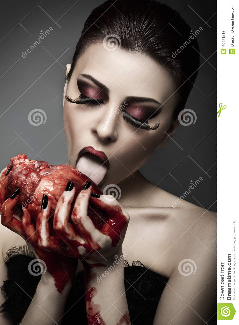 Beauty young woman licks blood from human heart