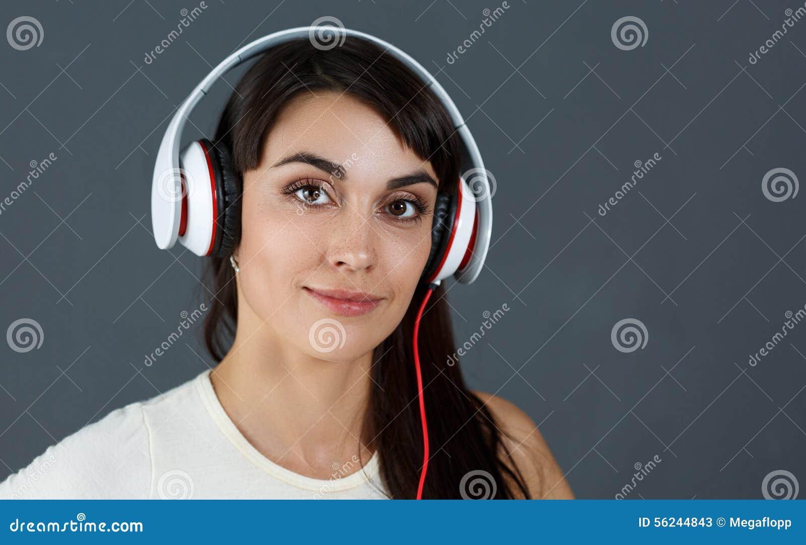 Beaux écouteurs de port de sourire d une chevelure foncés de femme