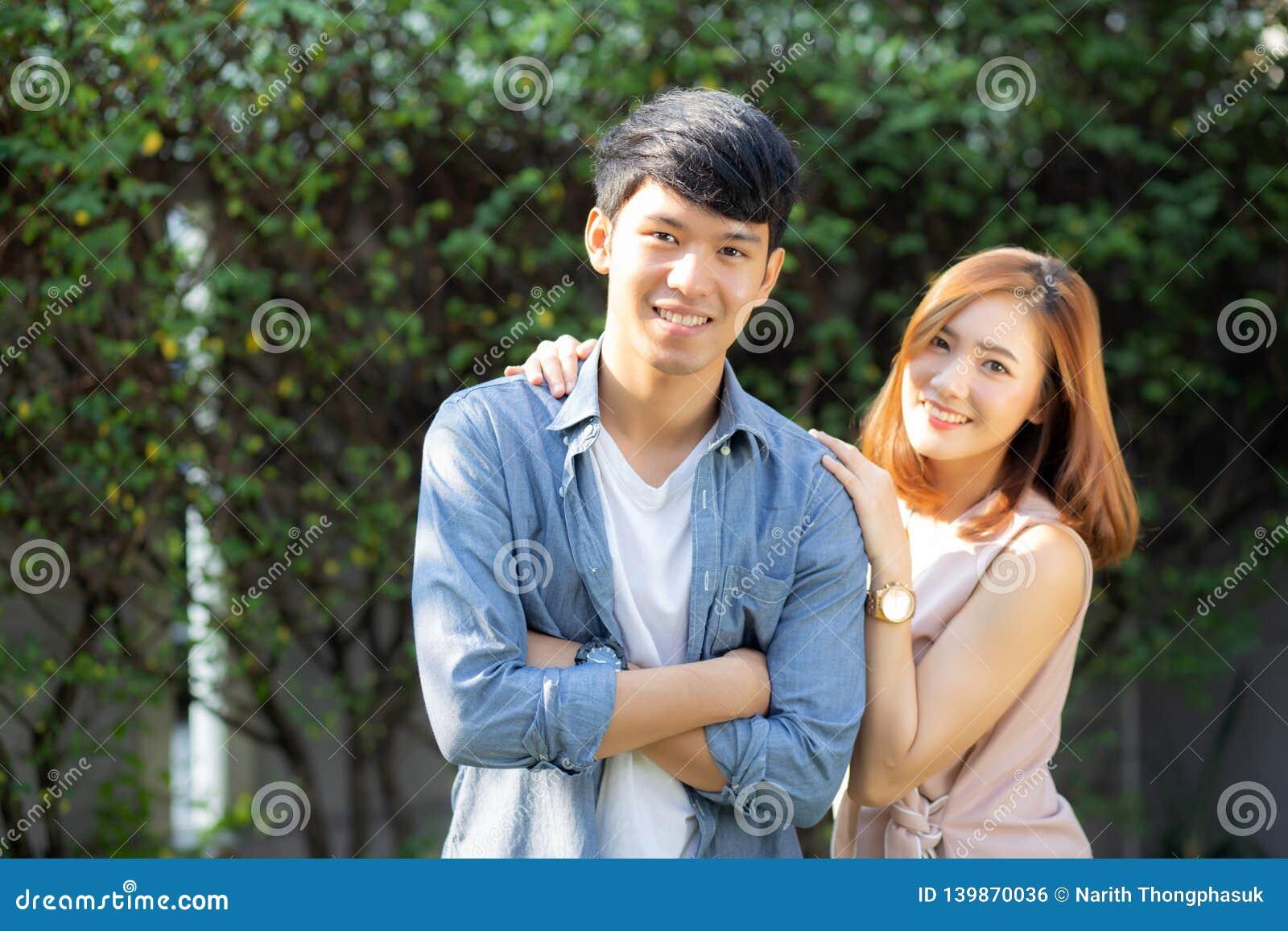 Beaux couples de portrait regardant chaque autres yeux et souriant avec l homme asiatique heureux et jeune et la relation de femm