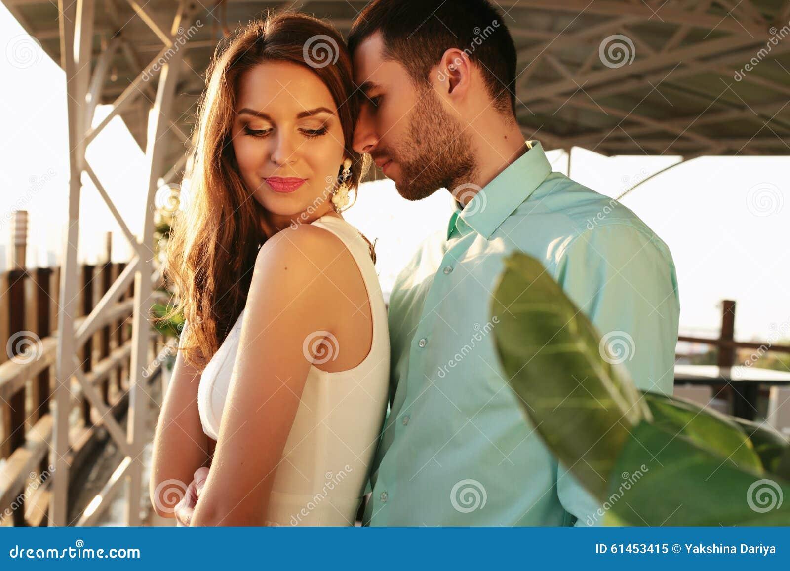 Beaux couples portant les vêtements élégants embrassant dans le restaurant extérieur