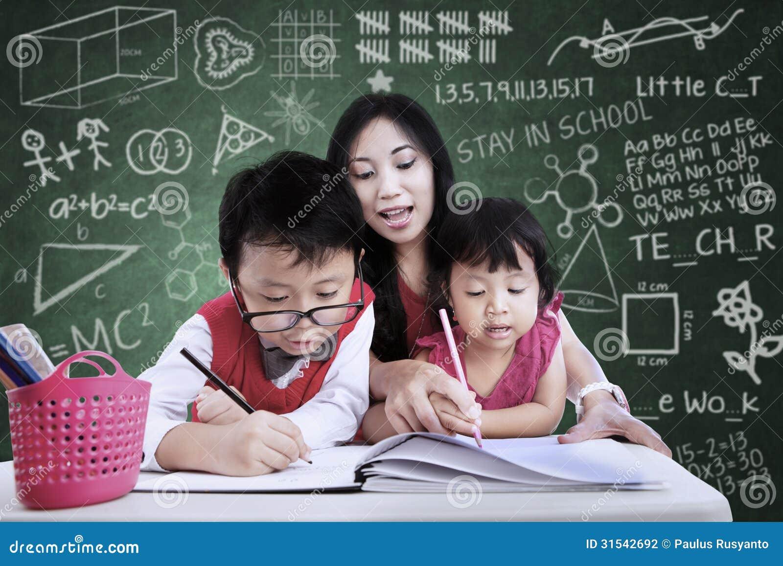 Beaux enfants d aide de professeur à écrire dans la classe