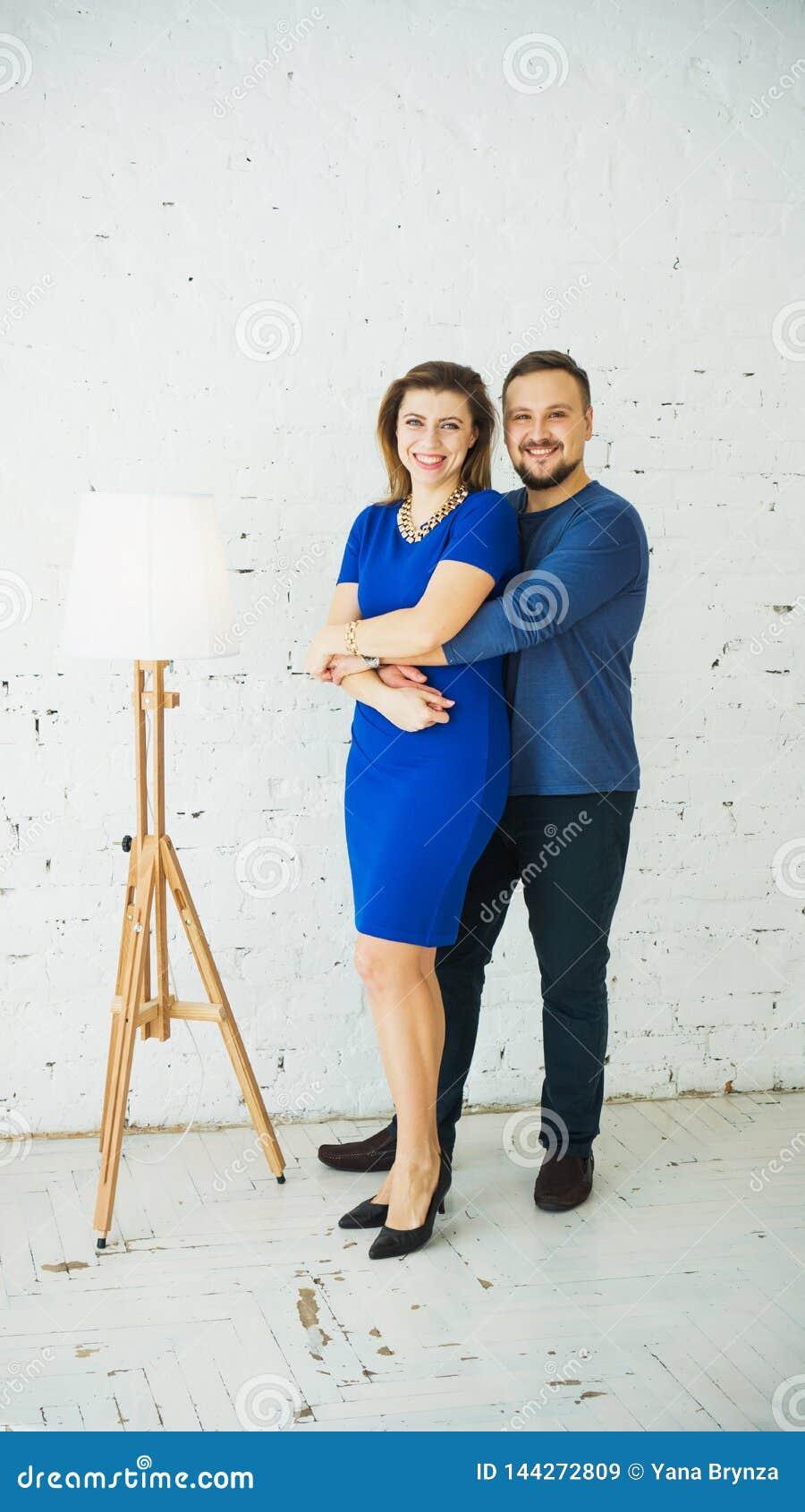 Beaux jeunes couples élégants à la maison étreignant et riant de la caméra Cadre vertical Robe bleue