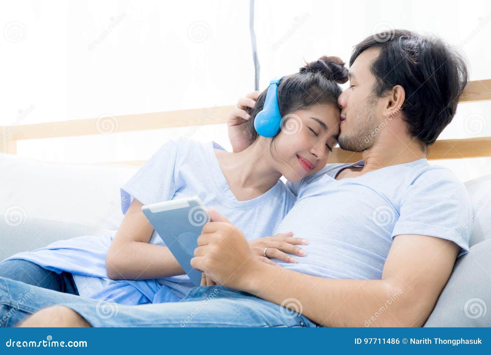 Beaux Jeunes Couples Asiatiques Ecoutant La Musique Avec Le Comprime