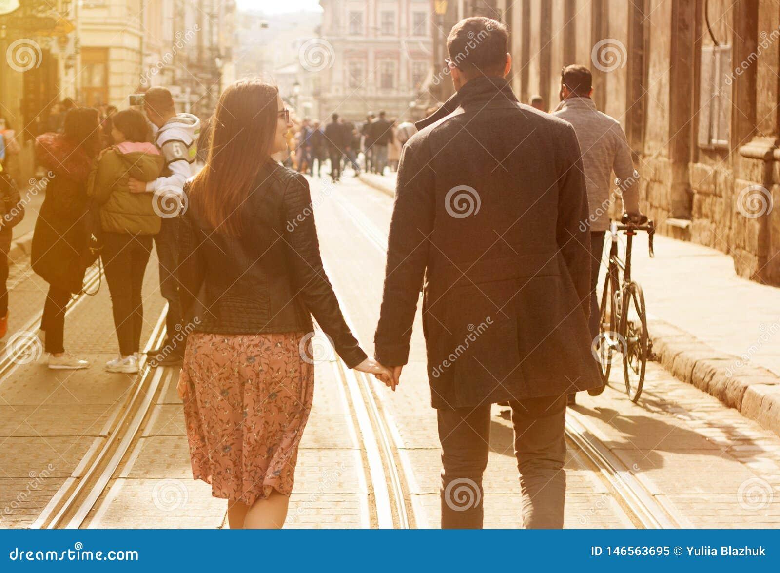 Beaux jeunes couples descendant la rue ensoleill?e