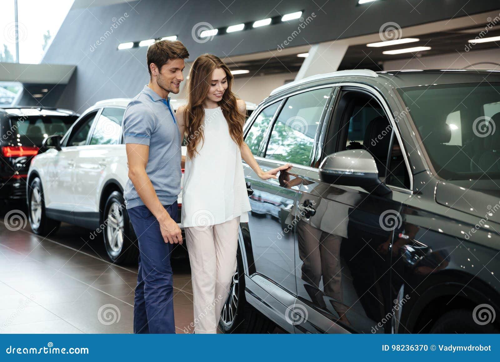 Beaux jeunes couples se tenant au concessionnaire automobile