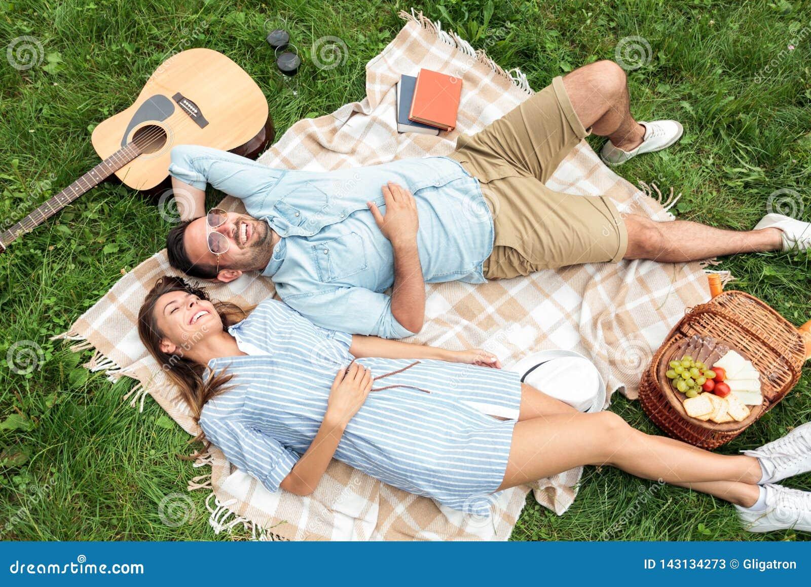 Beaux jeunes couples se trouvant l un à côté de l autre et détendant sur une couverture de pique-nique, appréciant leur jour à pa