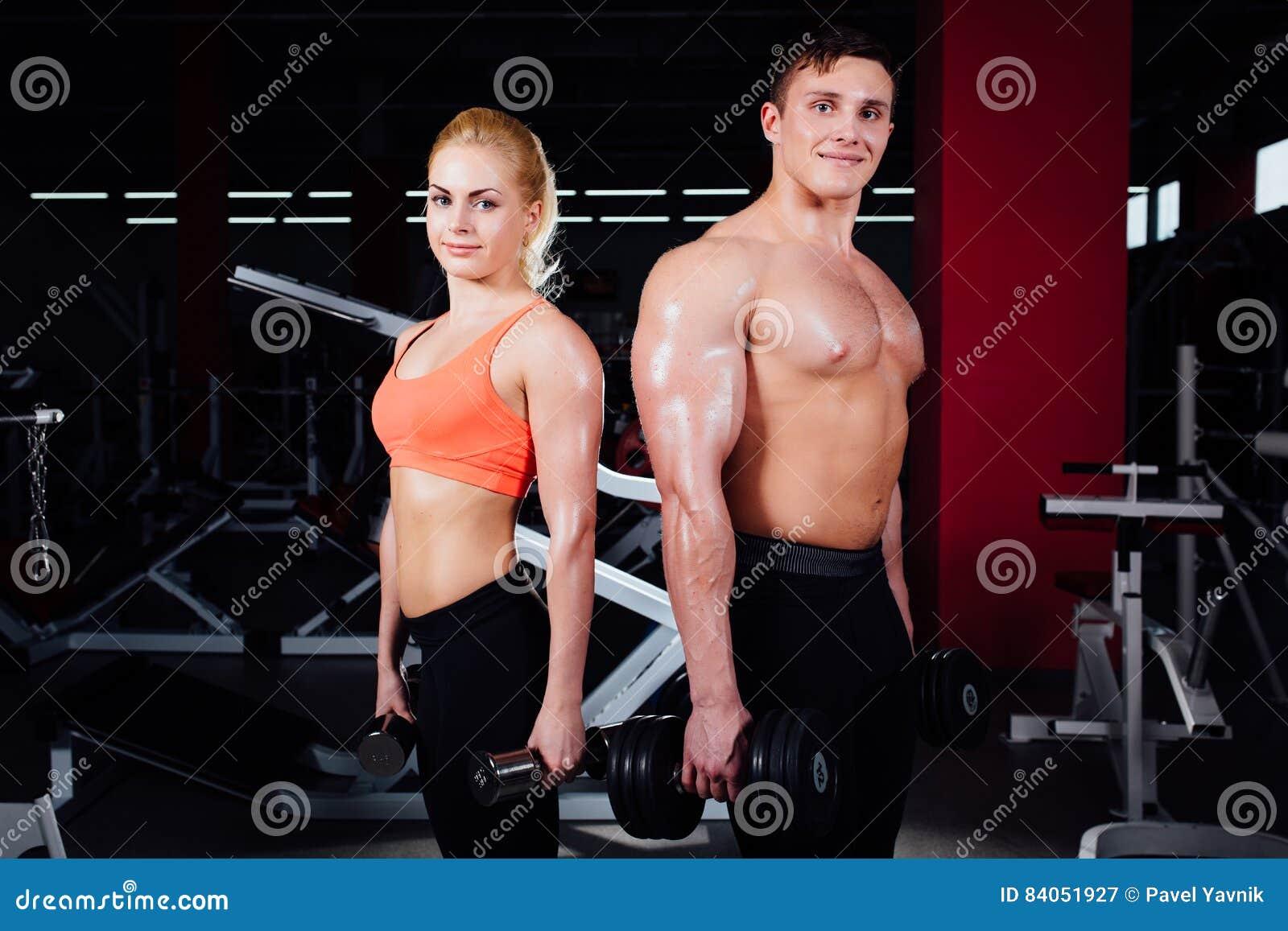 Beaux jeunes couples sportifs montrant le muscle et posant avec des haltères dans le gymnase pendant photoshooting