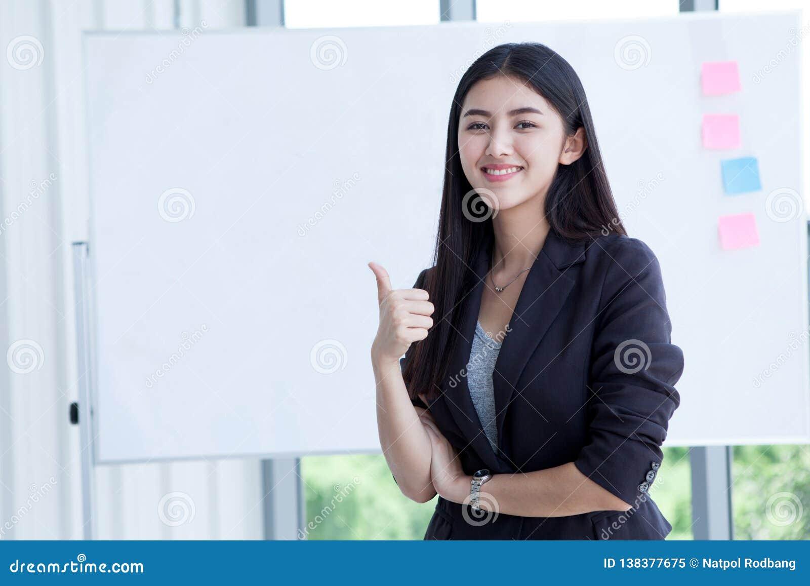 Beaux jeunes pouces asiatiques de sourire heureux d exposition de femme d affaires d isolement sur le fond de conseil blanc dans