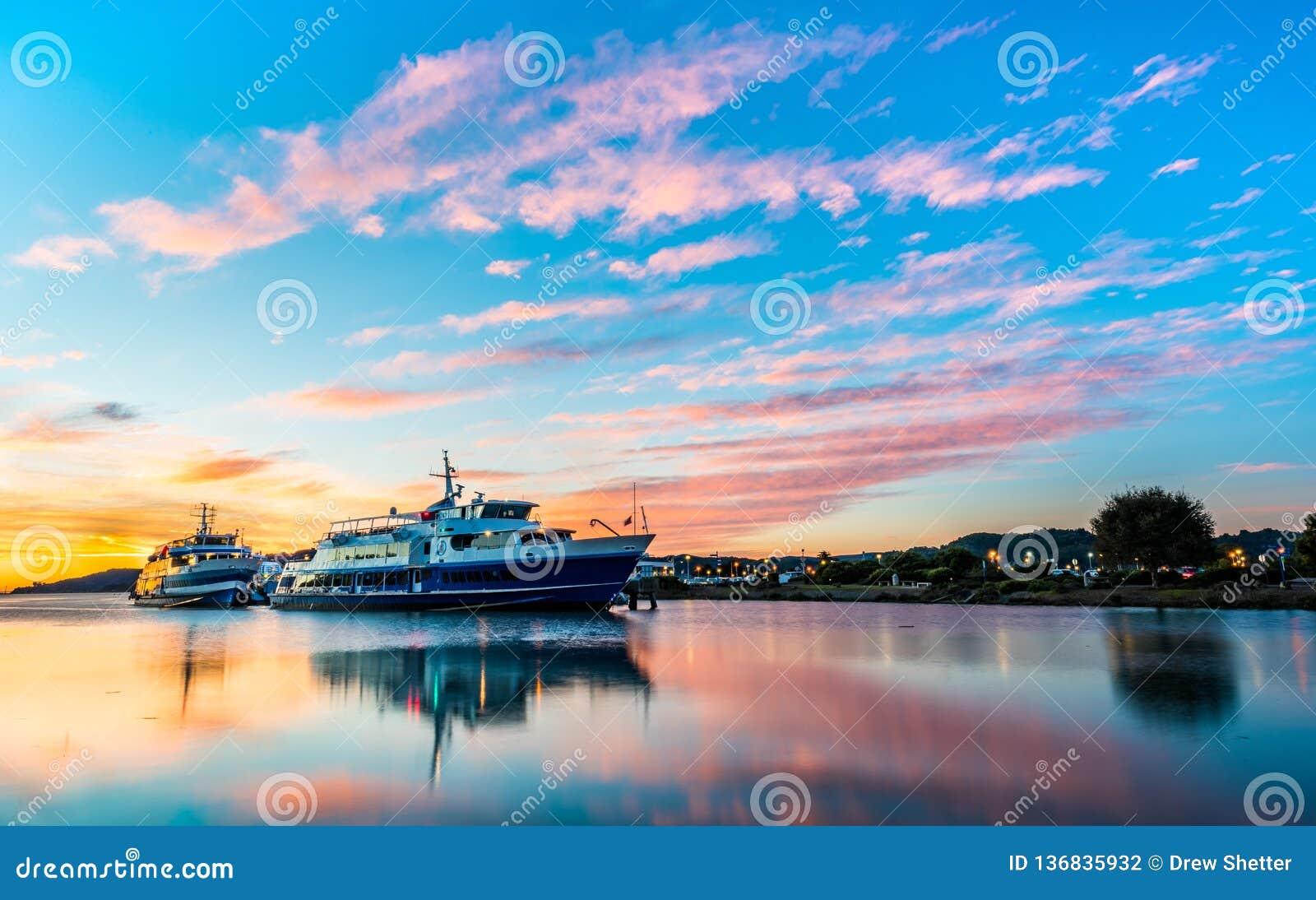 Beaux nuages de lever de soleil avec de l eau lisse de pied-d alouette, ferries de CA