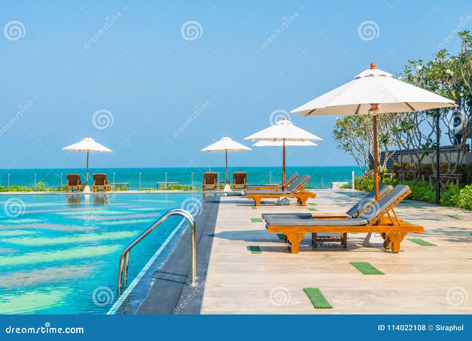 beaux parapluie et chaise autour de piscine dans l'hôtel et le r