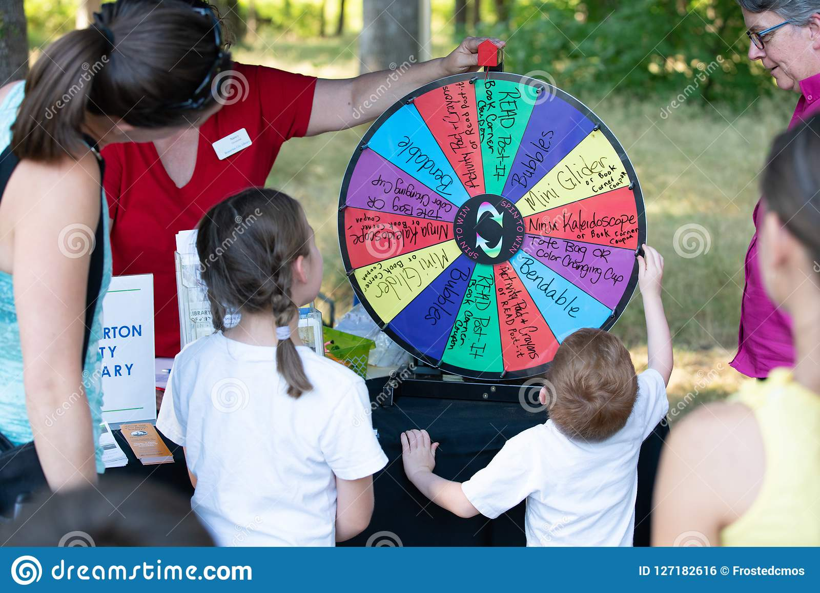 Child spinning the wheel raffle in the park