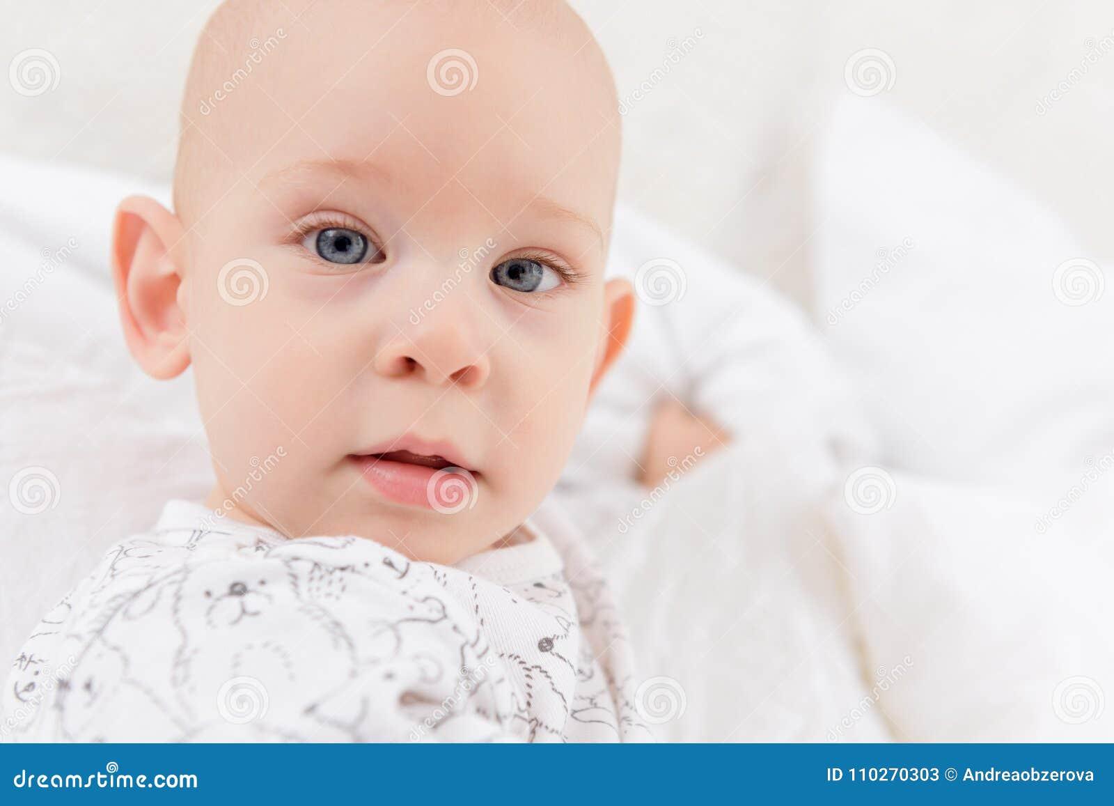 Bebé adorable con los ojos azules que miran directamente la cámara que intenta alcanzar para ella Cierre lindo del niño para arri