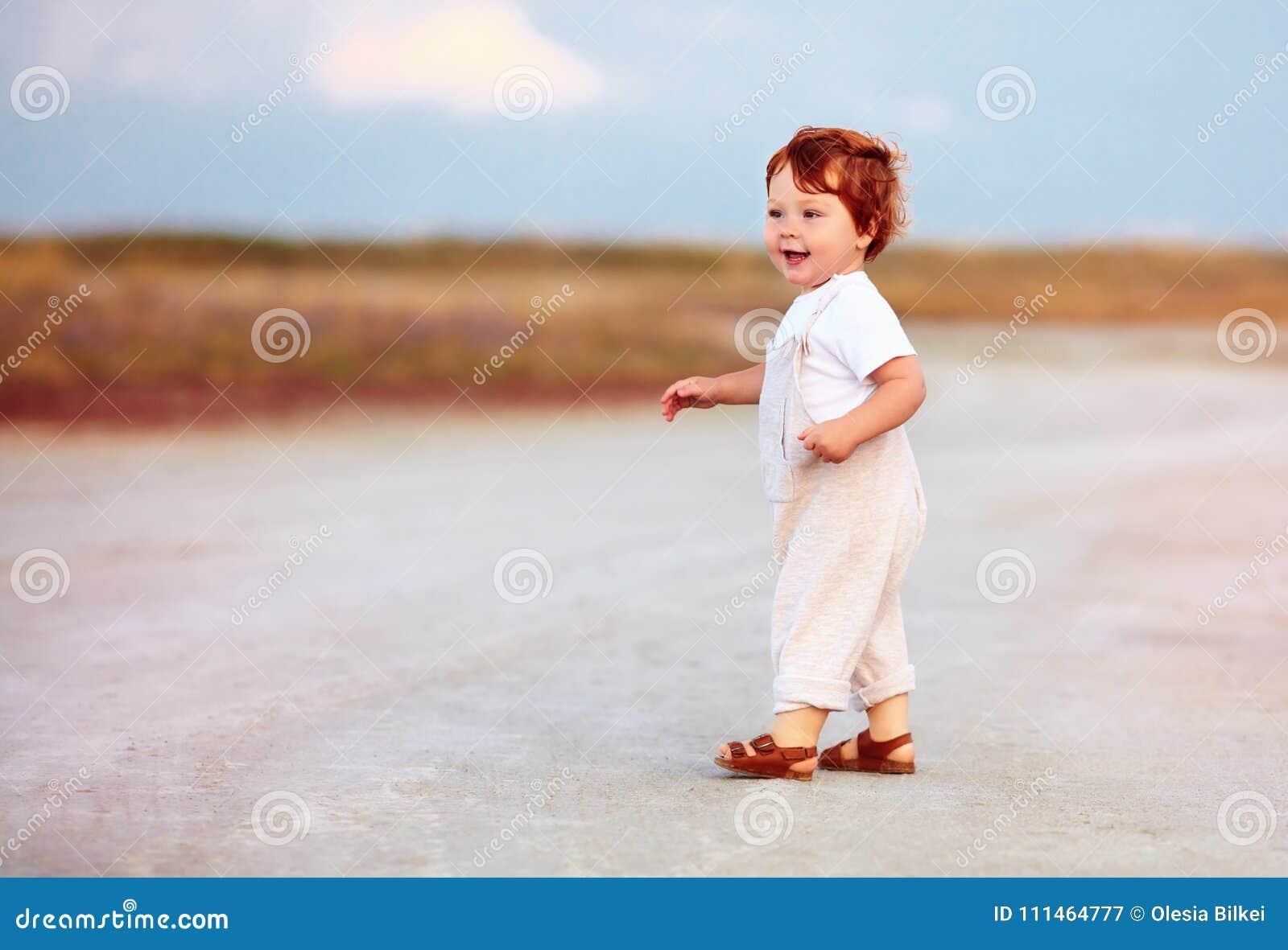 Bebé adorable del niño del pelirrojo en mono que camina a través del camino y del campo del verano