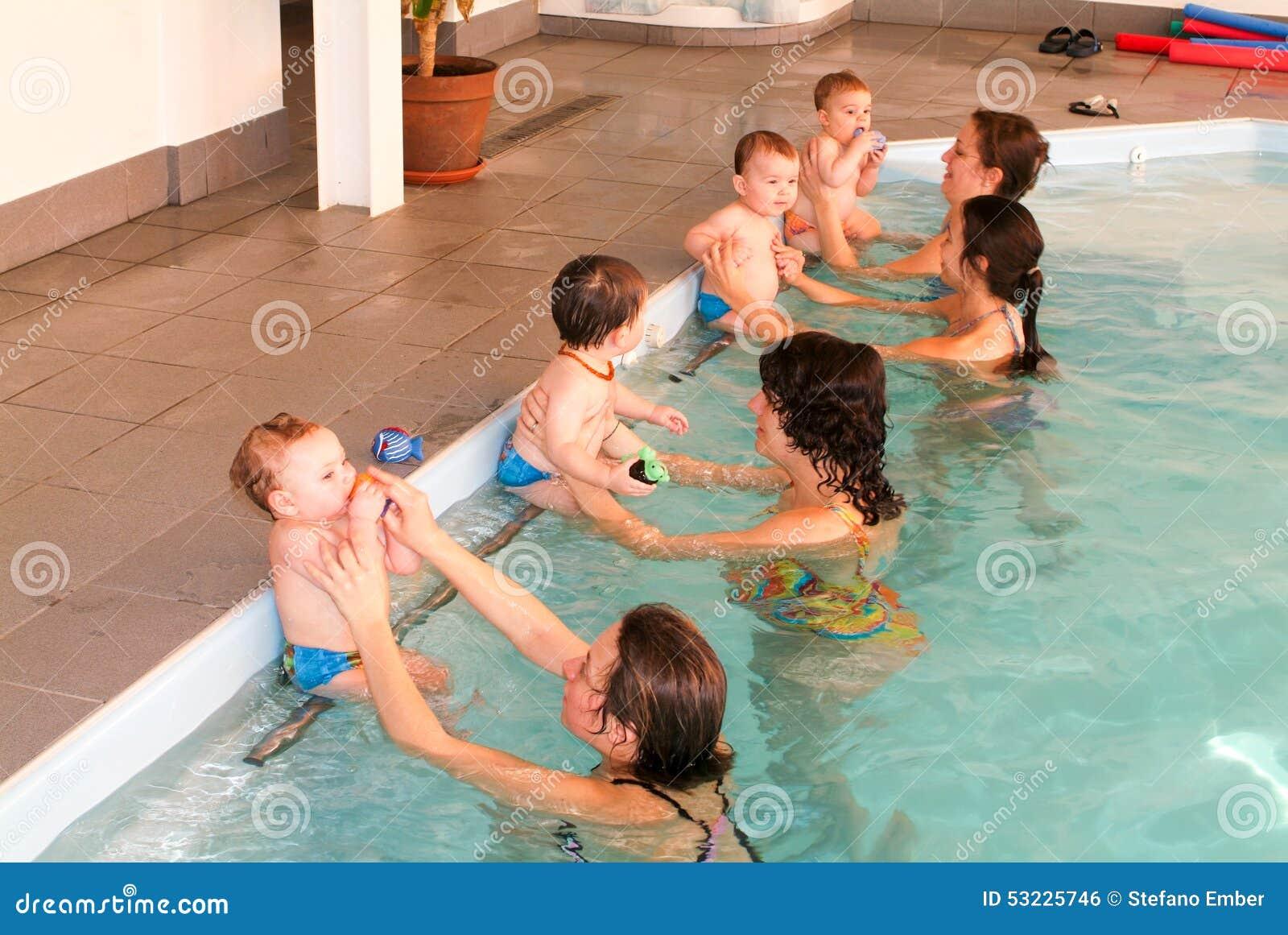Bebé adorable que disfruta de nadar en una piscina con su madre