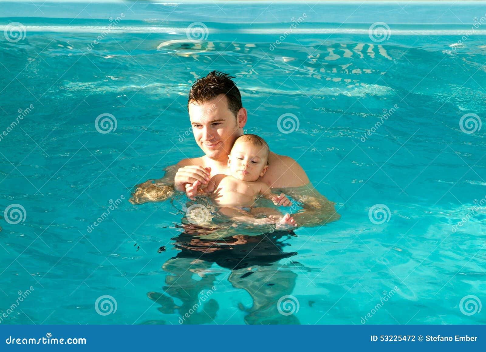 Bebé adorable que disfruta de nadar en una piscina con su padre