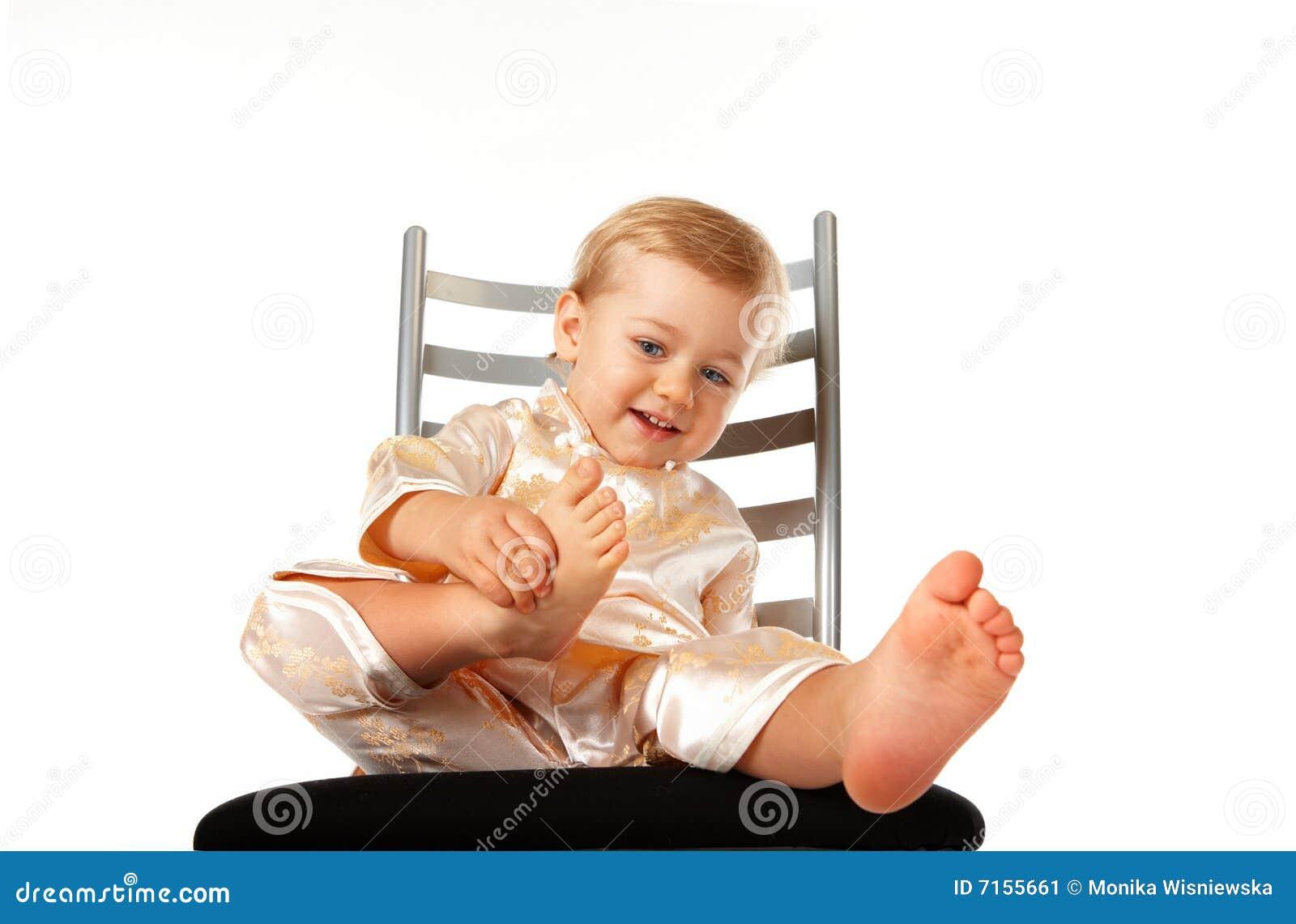 Bebé adorable que se sienta en una silla