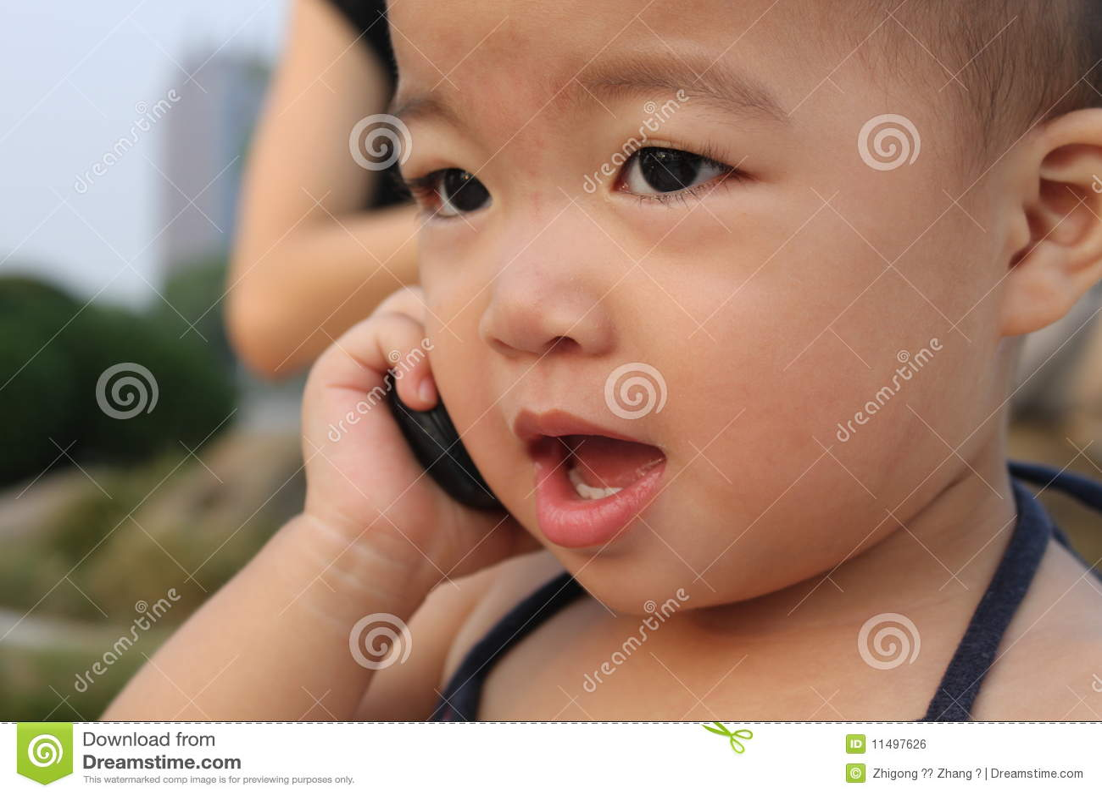 Bebé asiático en el juego de la honda, murmurando a un teléfono celular