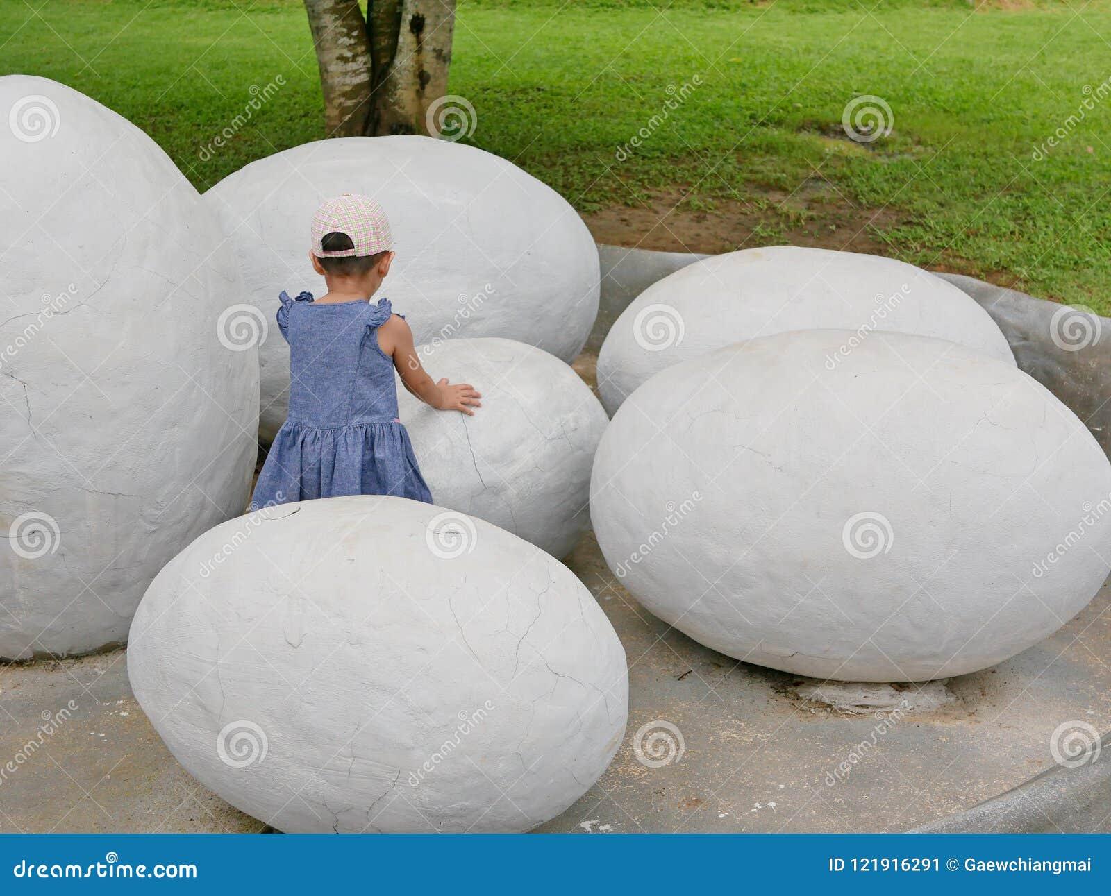 695c9e7d5d4c Bebé asiático que toca un huevo de dinosaurio para explorar si ella siente  cualquier cosa dentro