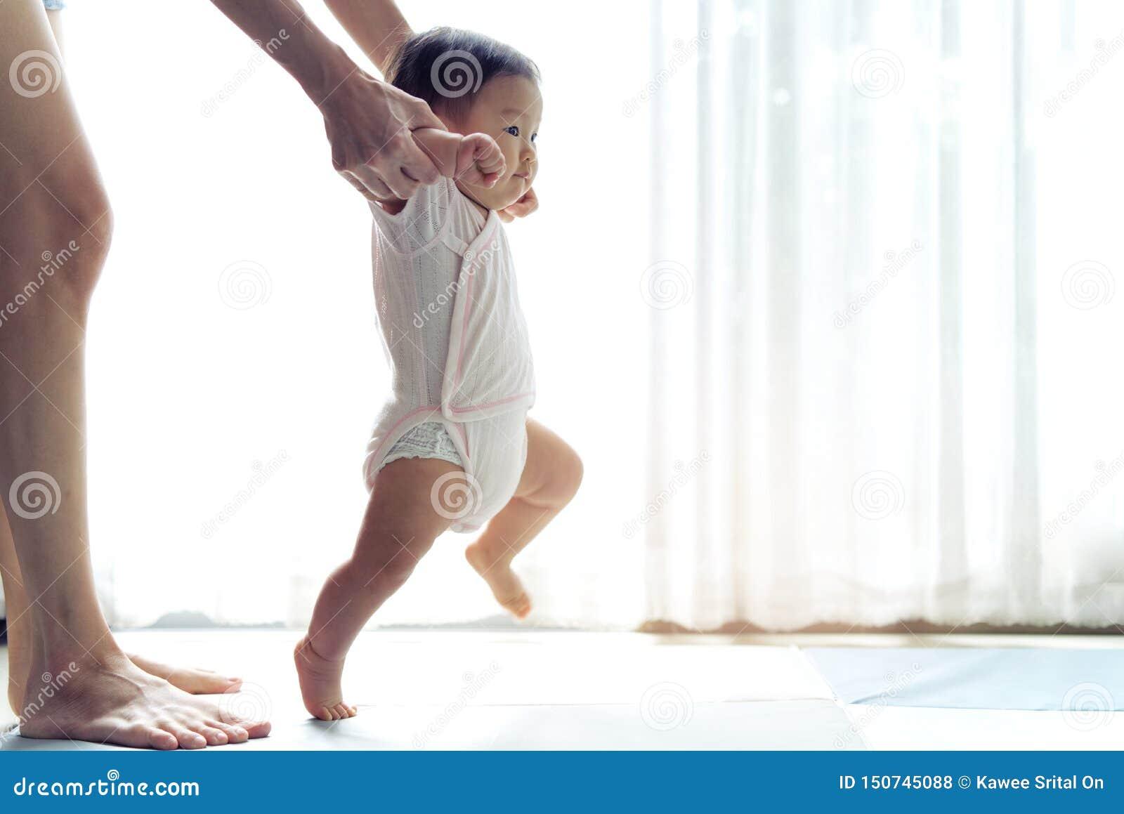 Bebé asiático que toma primero medidas para caminar adelante en la estera suave