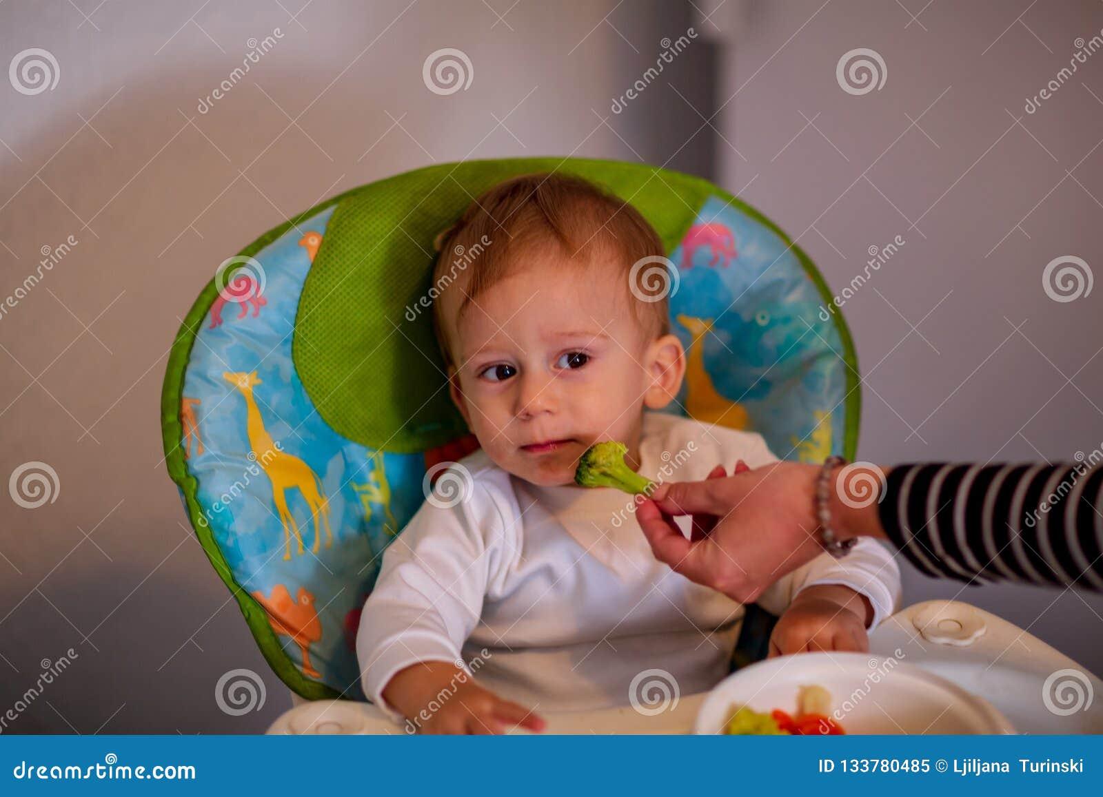 Bebé de alimentación con las verduras - el bebé lindo rechaza comer el bróculi