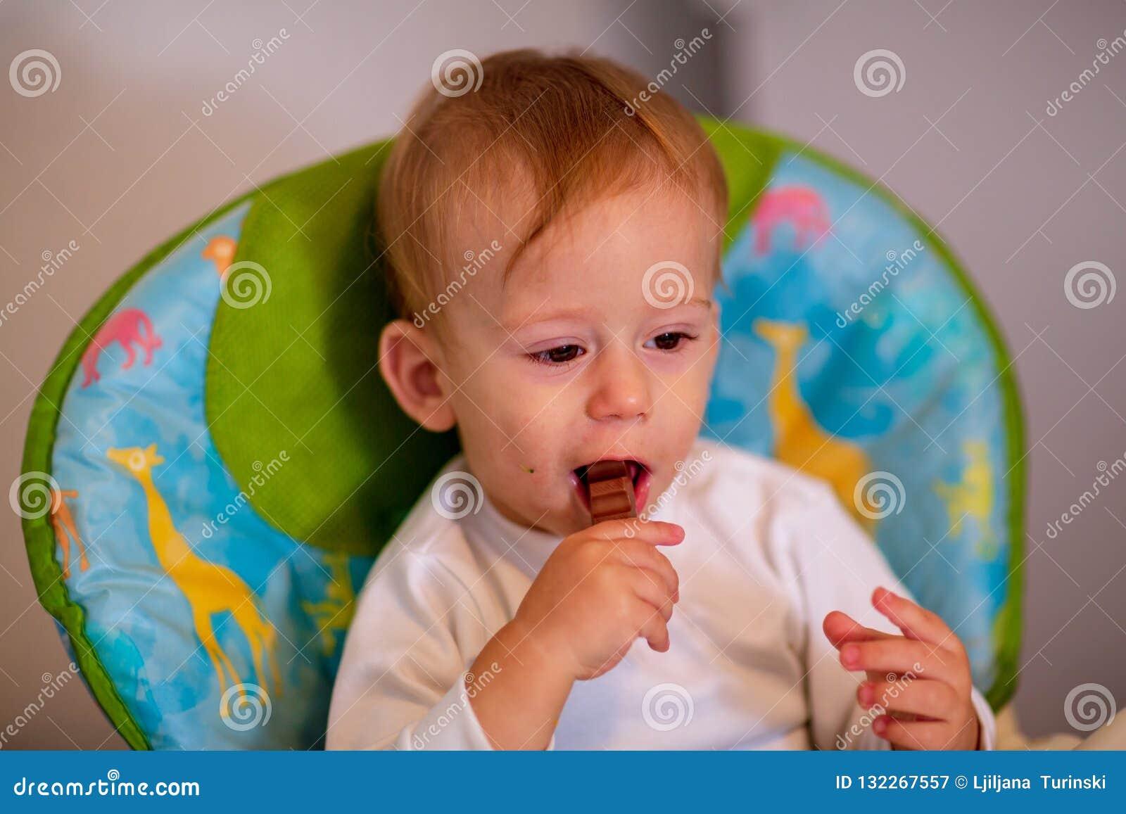 Bebé de alimentación - muchacho adorable que come el chocolate