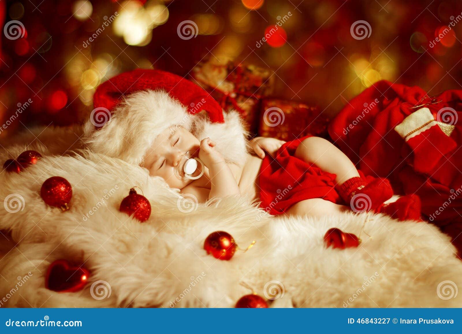 Bebé de la Navidad, niño recién nacido que duerme como regalo de Navidad en Santa Hat