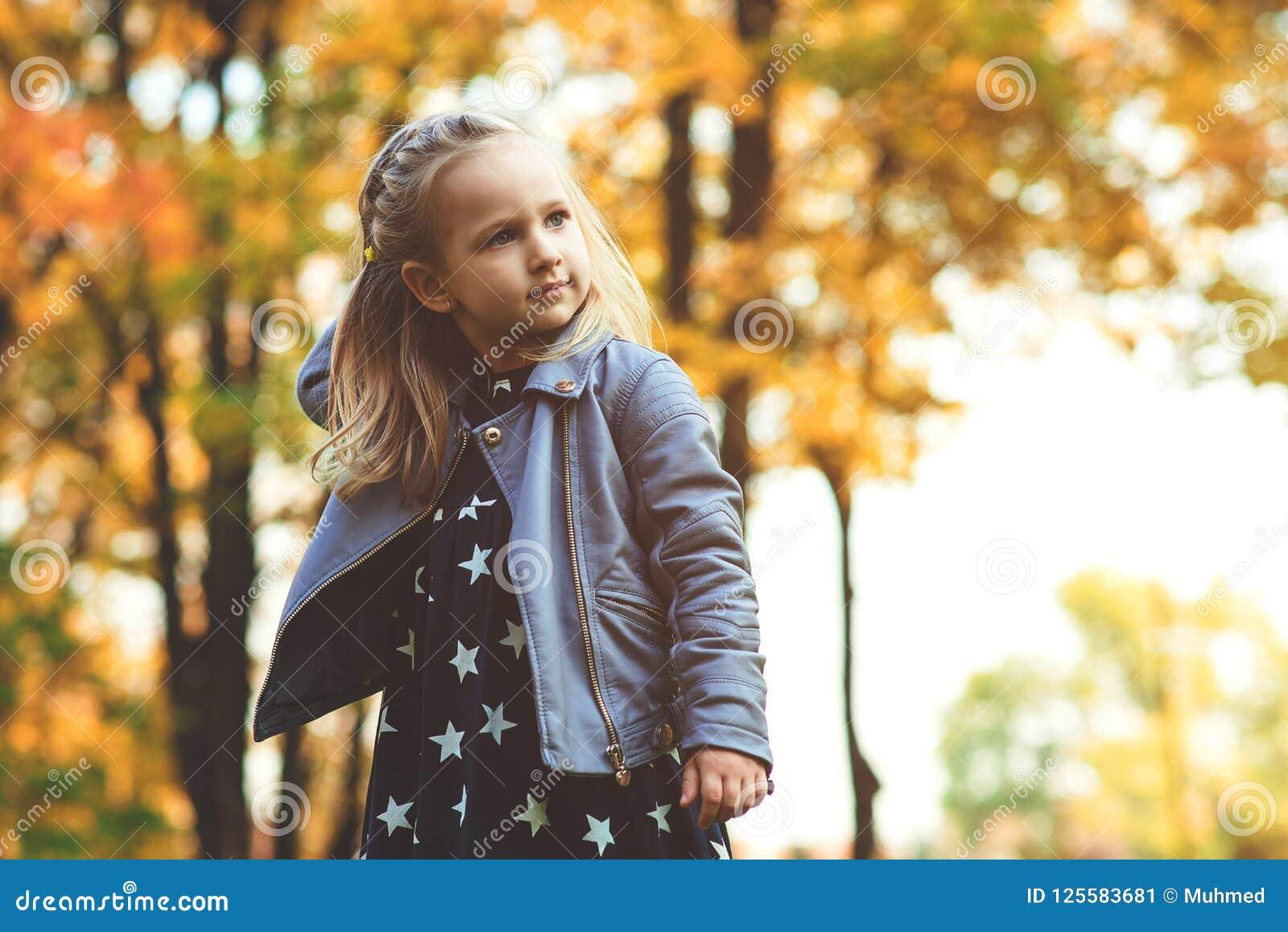 Bebé de moda hermoso que camina en parque del otoño Niño feliz que juega al aire libre en otoño La niña elegante goza de DA solea