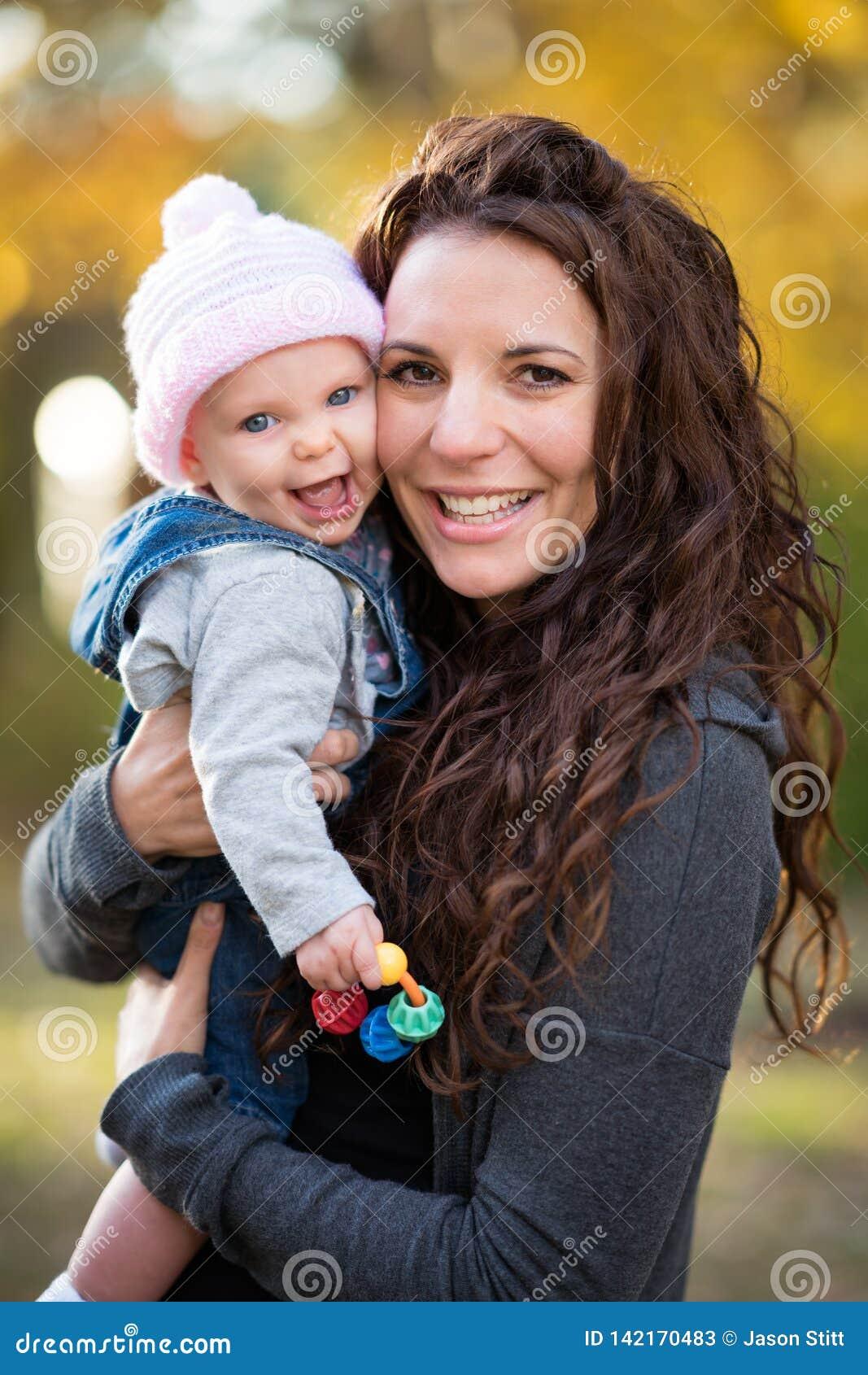 Bebé de risa de la tenencia de la mamá
