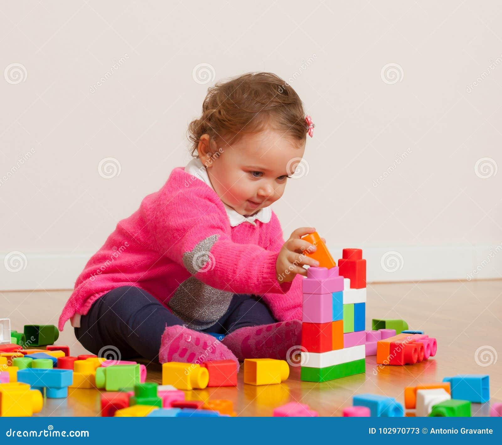 Bebé del niño que juega con las unidades de creación de goma