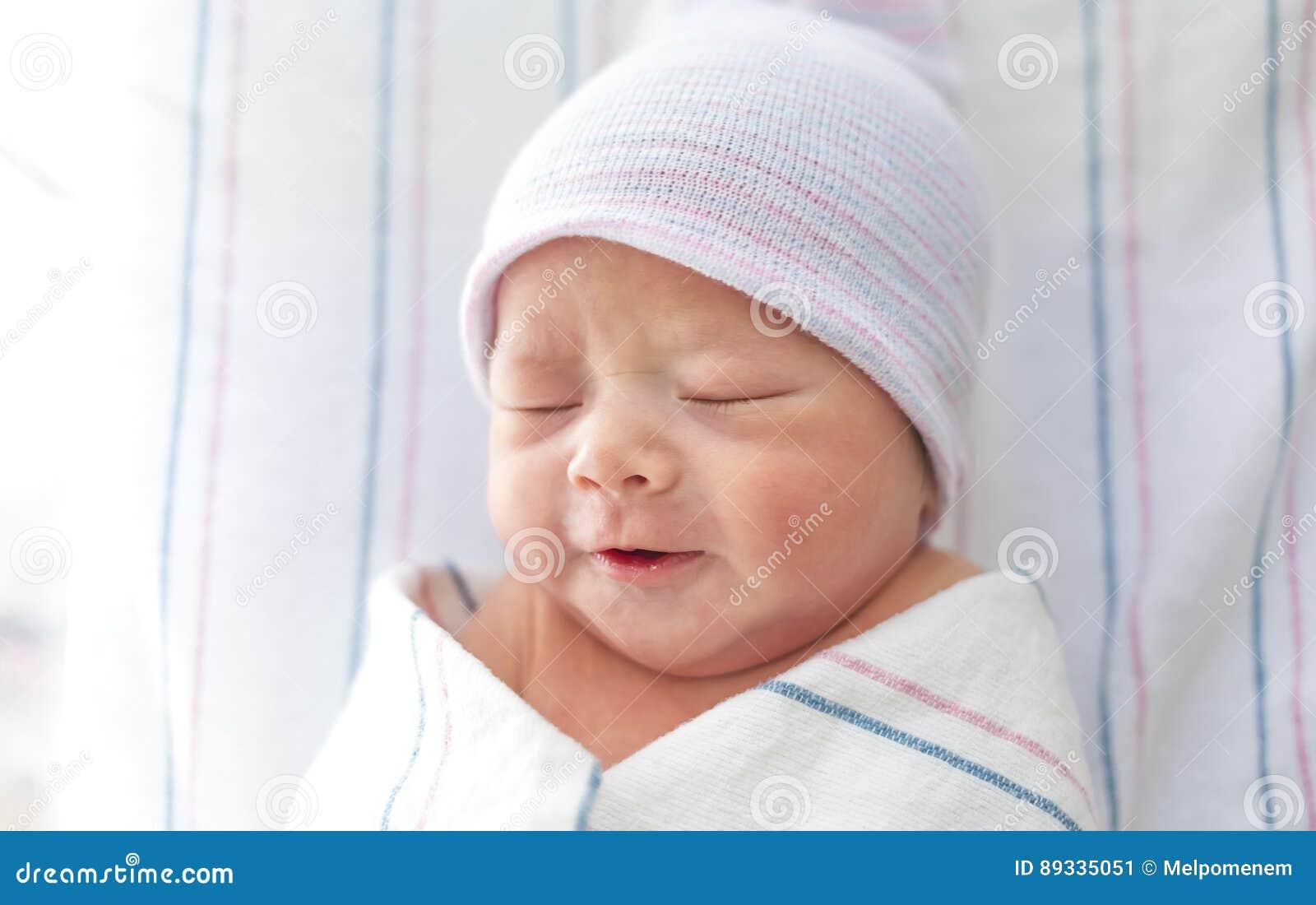 7d3168f5 Bebé del niño recién nacido puesto los pañales después del nacimiento que  miente en su cama de hospital