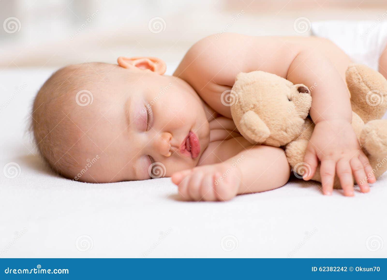 Bebé despreocupado del sueño con el juguete suave