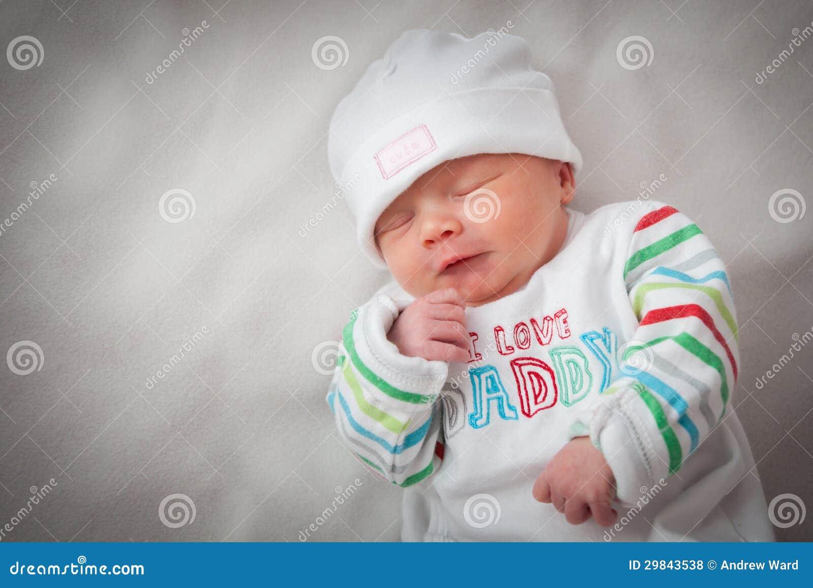 Bebé recém-nascido bonito que dorme, com seu han