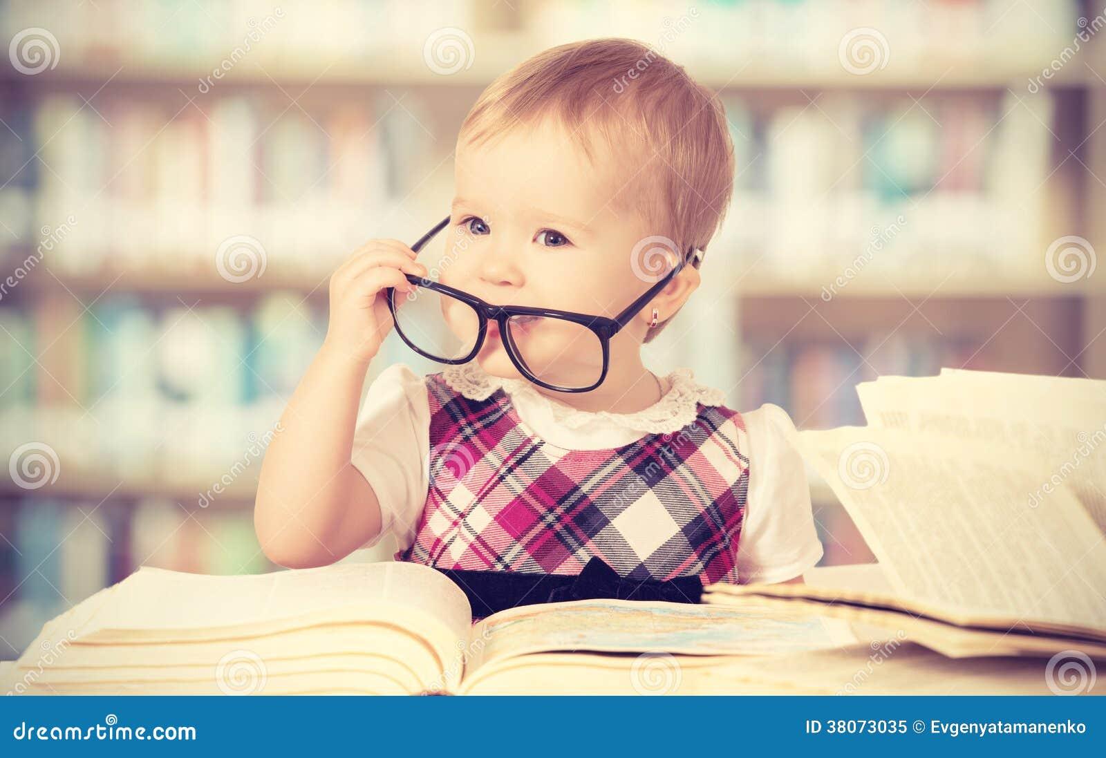 Bebé divertido en vidrios que lee un libro en una biblioteca