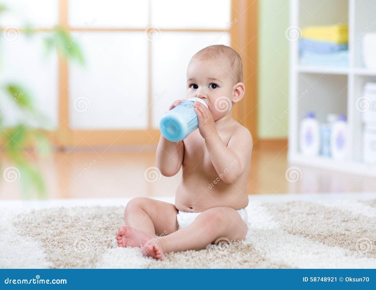 Bebé dulce que sostiene la botella y la leche de consumo