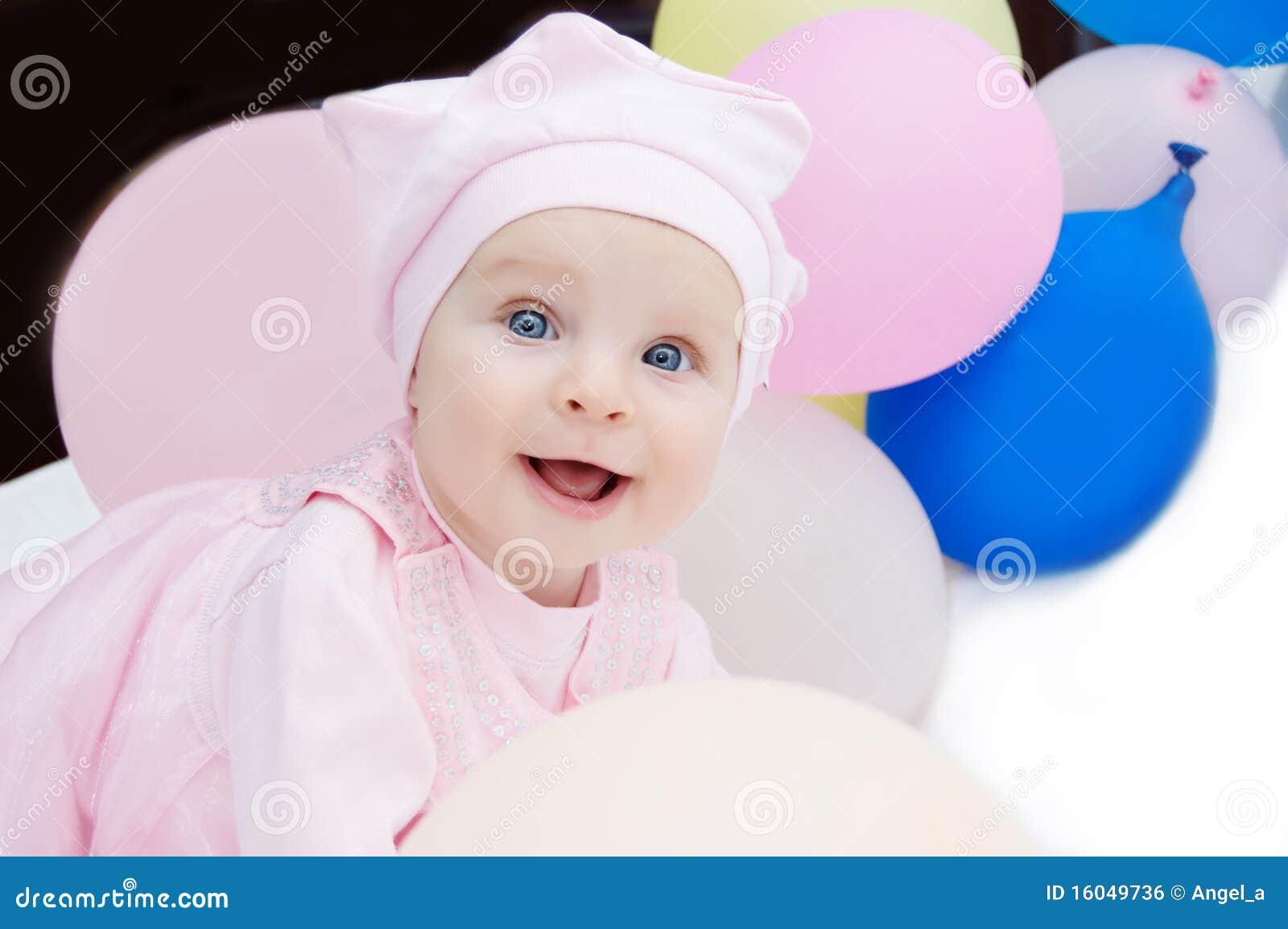 Bebé en color de rosa con los globos